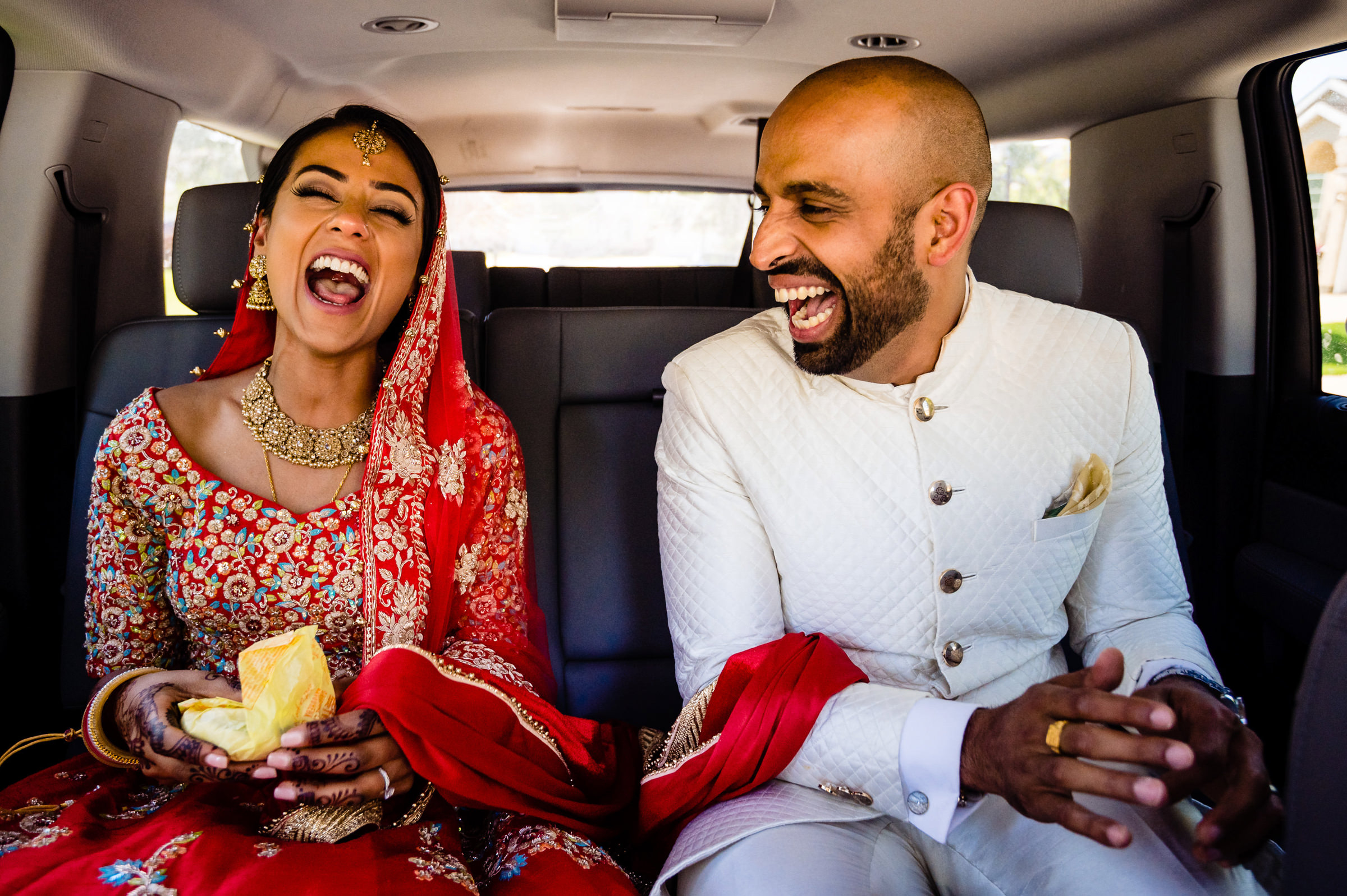 Hilarious photo of laughing bride and groom in limo - photo by Moore Photography