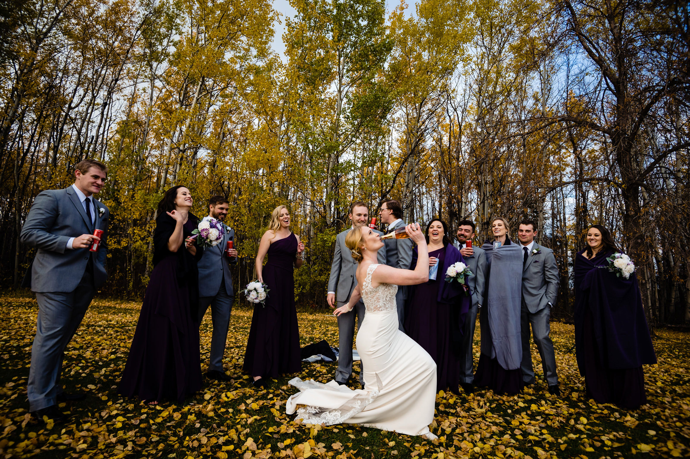 kneeing bride drinking from a bottle with wedding  party outdoors - photo by Moore Photography