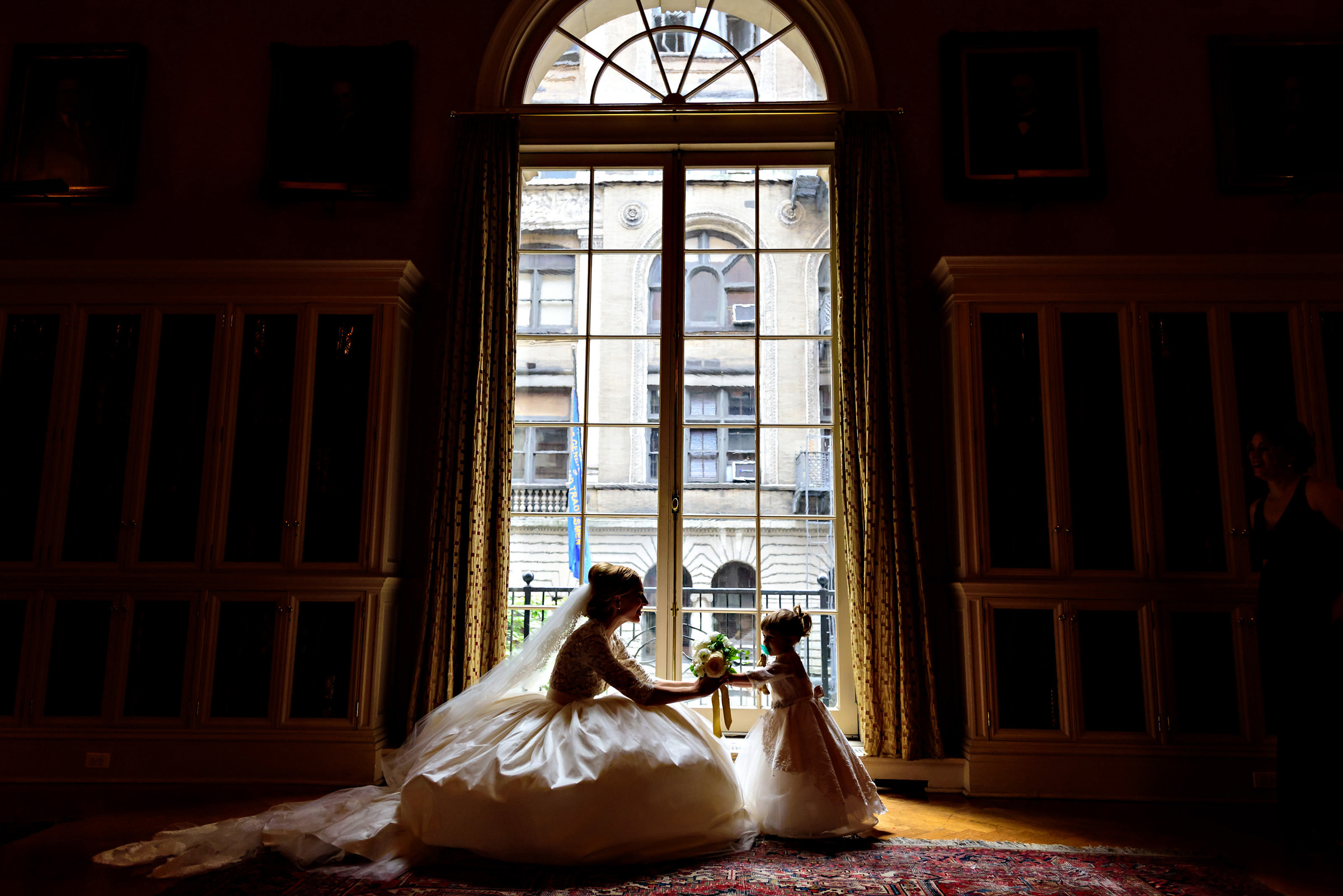 Little girl hands bouquet to bride in front of arched window - photo by Moore Photography