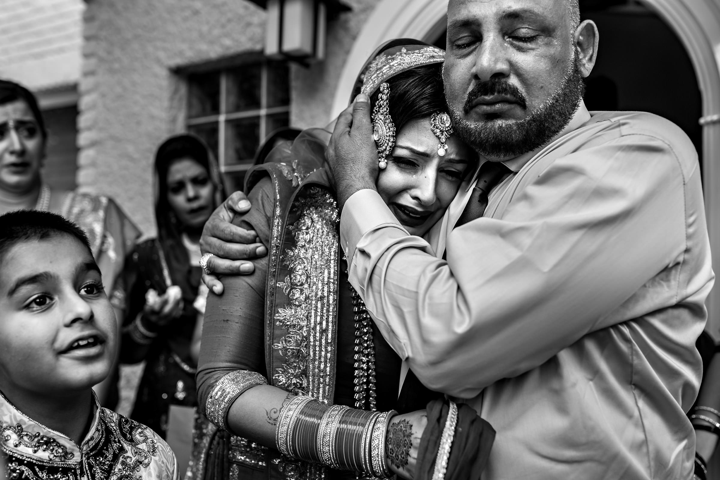 Muslim bride and father embrace - photo by Moore Photography