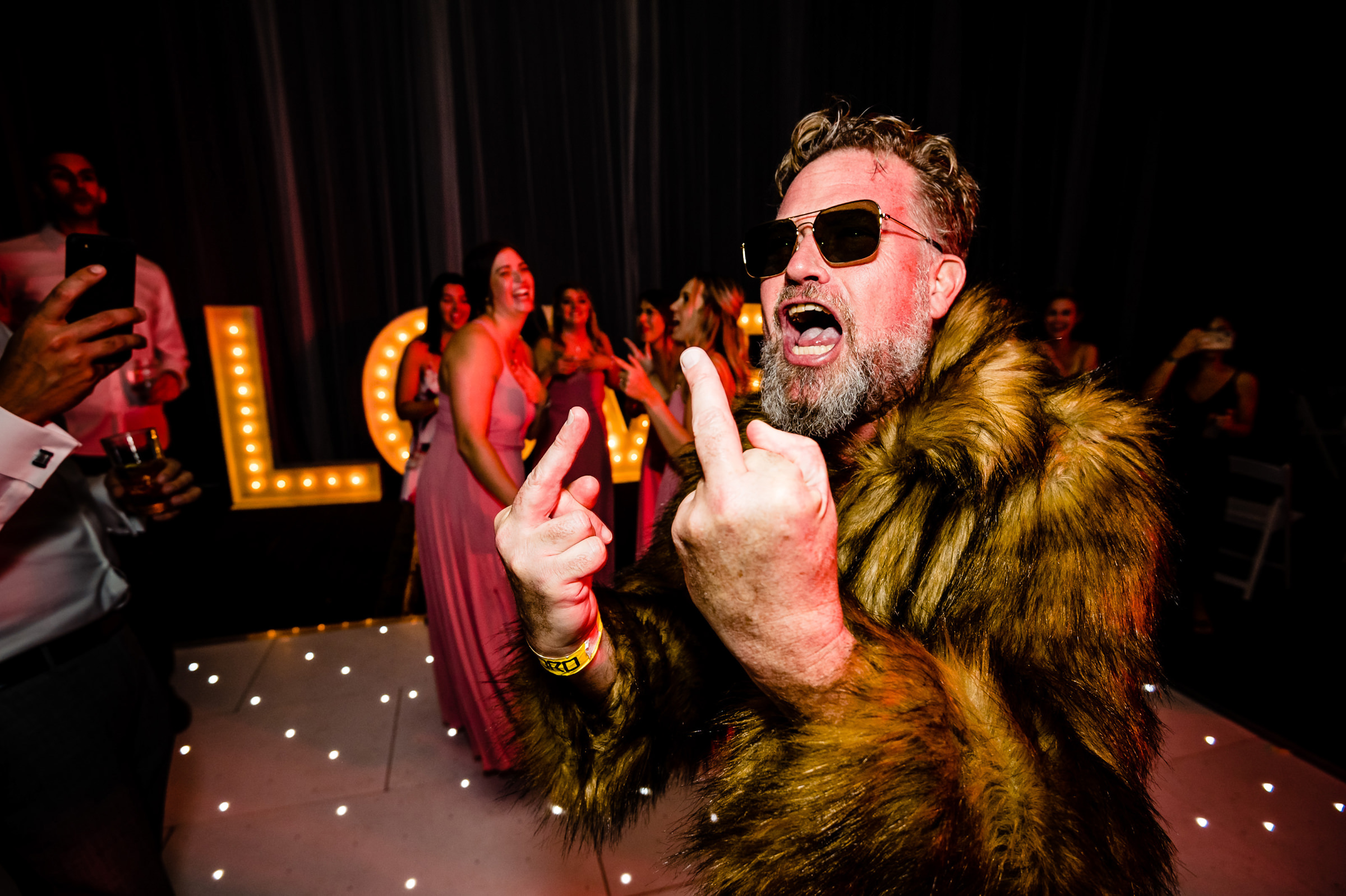 Party guest in fur coat with two middle fingers up - photo by Moore Photography