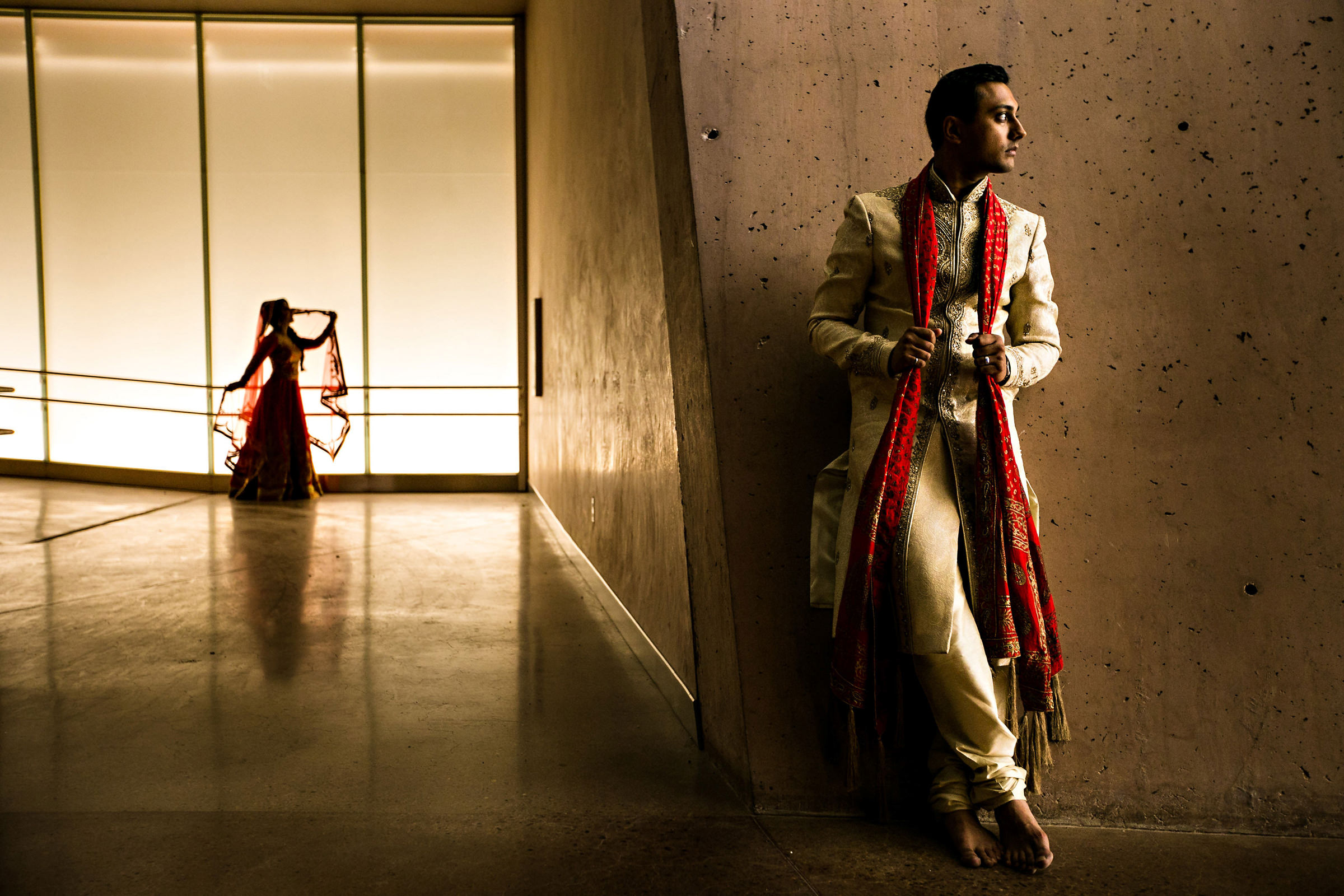 Portrait of Indian groom with bride in background - photo by Moore Photography