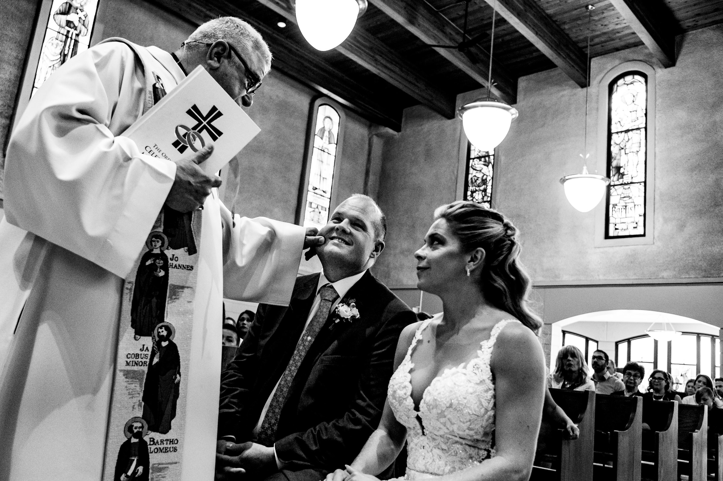 Priest pinches cheek of groom - photo by Moore Photography