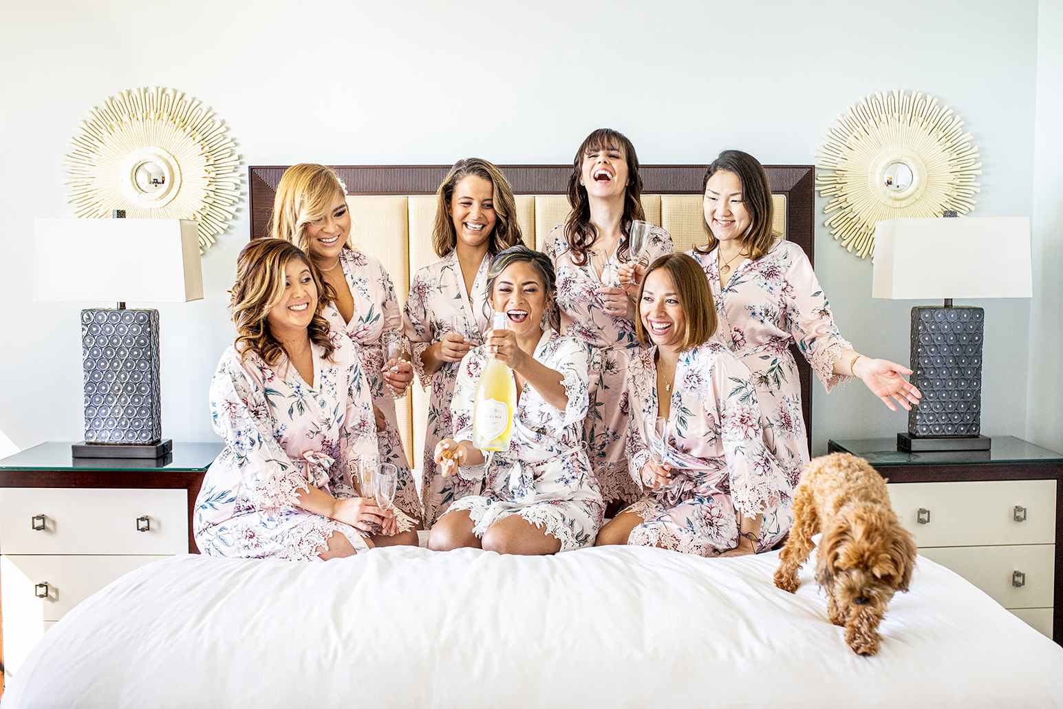 Bride and bridesmaids pop champagne with puppy - photo by Anna Schmidt Photography