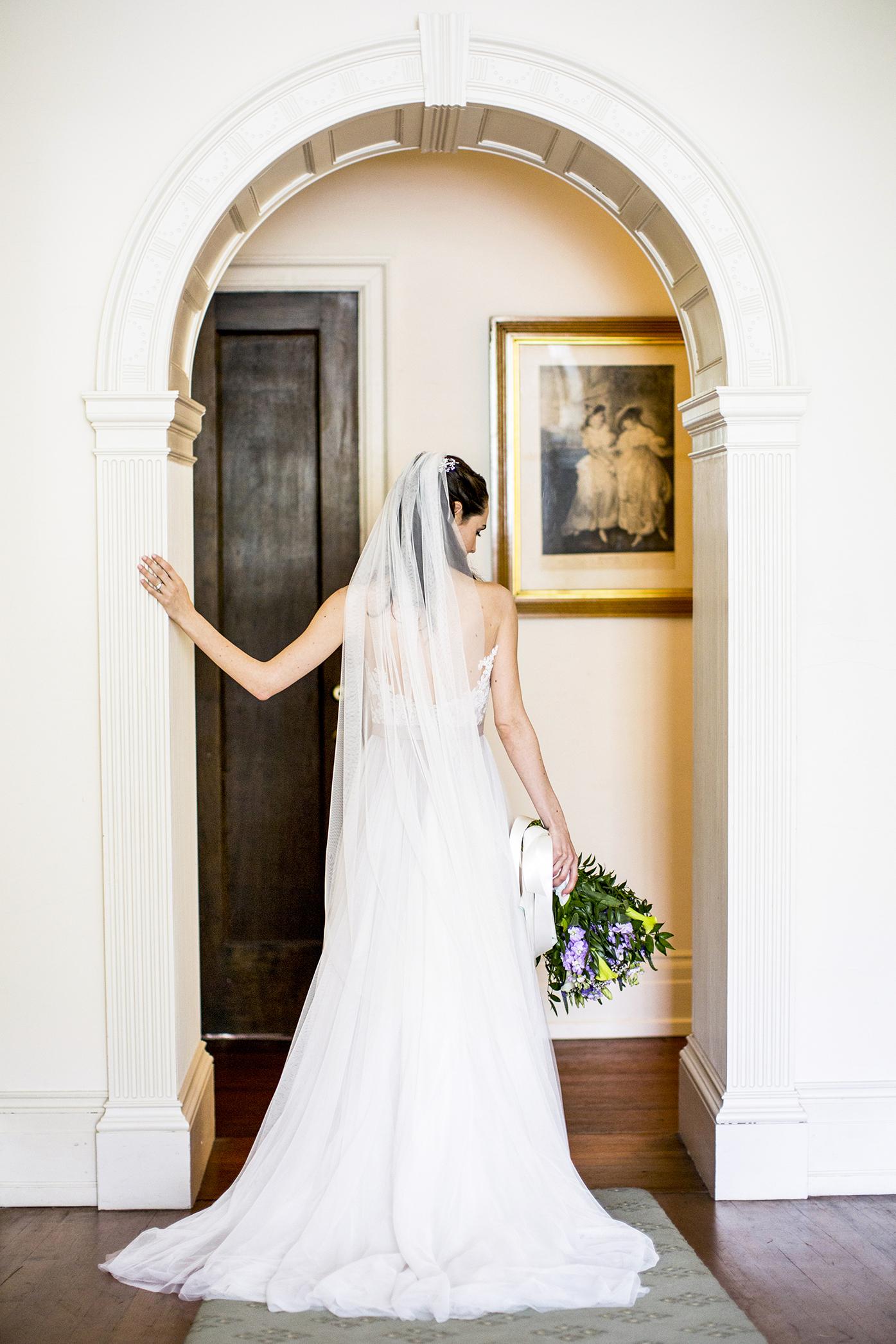 Bride in doorway wearing long veil - photo by Anna Schmidt Photography