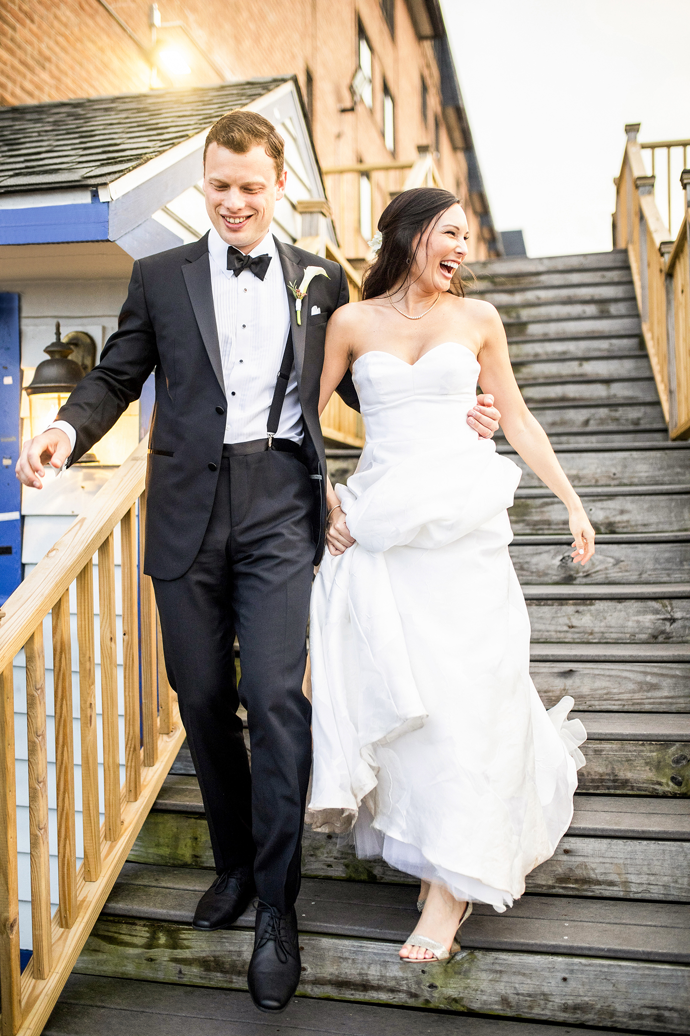 Happy bride in strapless gown with groom descending wooden stairs - photo by Anna Schmidt Photography