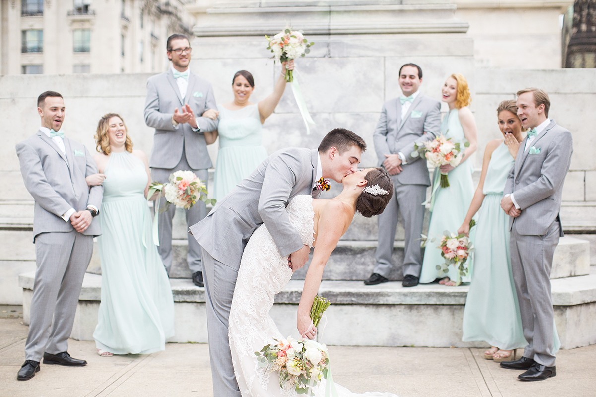 Bride and groom kiss with wedding party cheering - photo by Anna Schmidt Photography