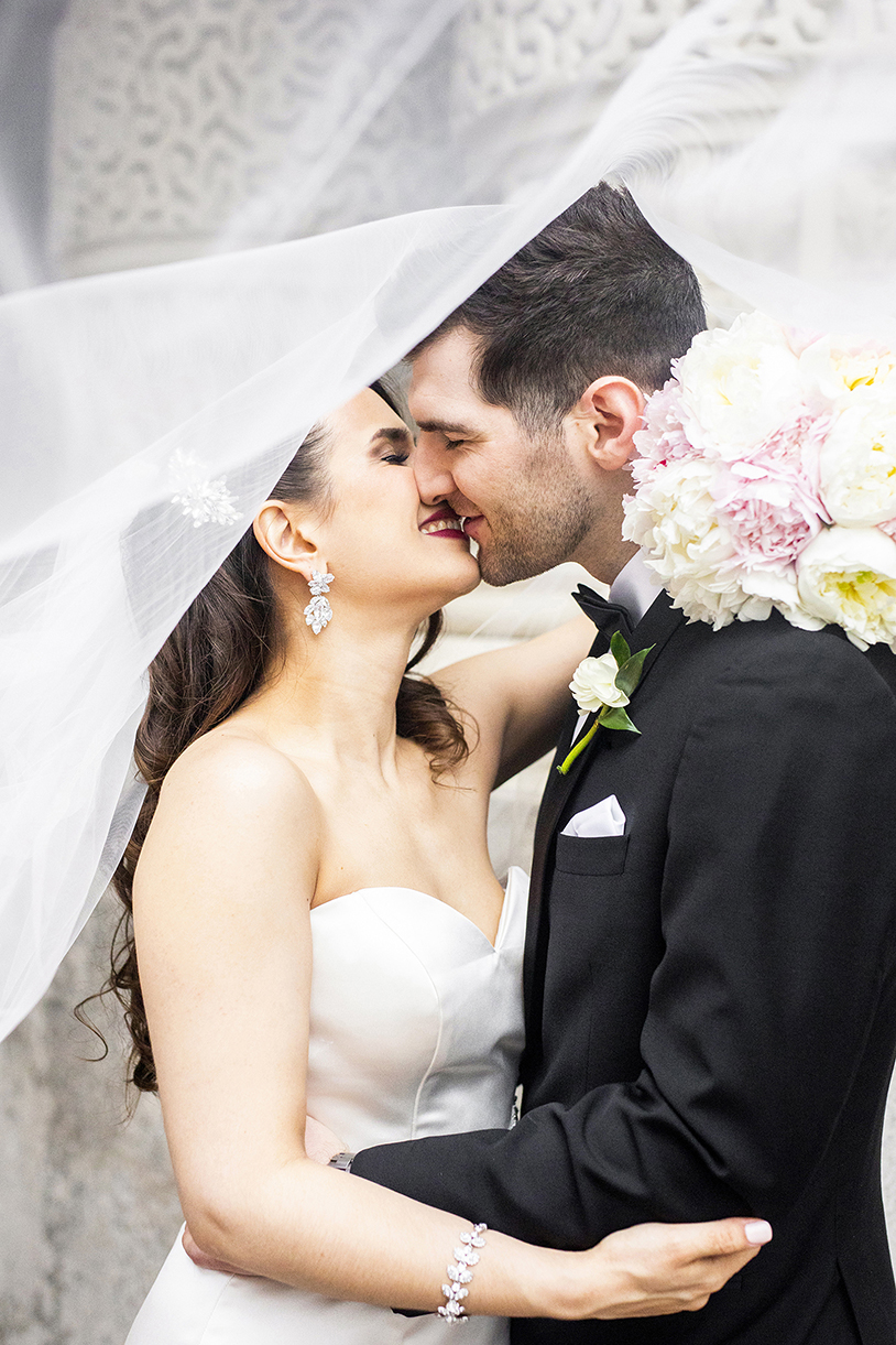 Bride with chandelier earrings and peoony bouquet kisses groom under veil - photo by Anna Schmidt Photography