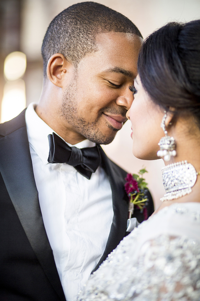Elegant couple face to face with bride wearing chandelier earrings and silver necklace - photo by Anna Schmidt Photography