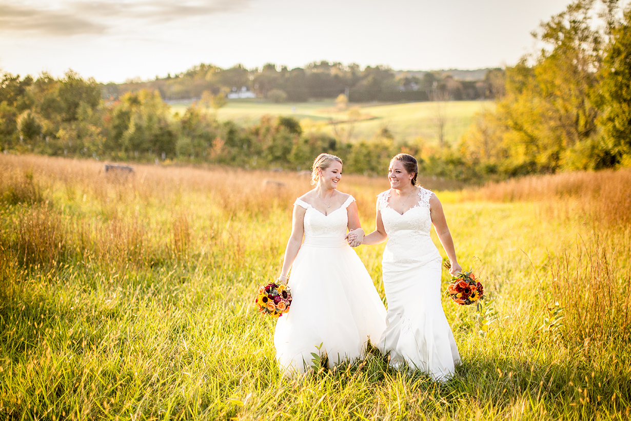 Two brides in sunlit field - photo by Anna Schmidt Photography