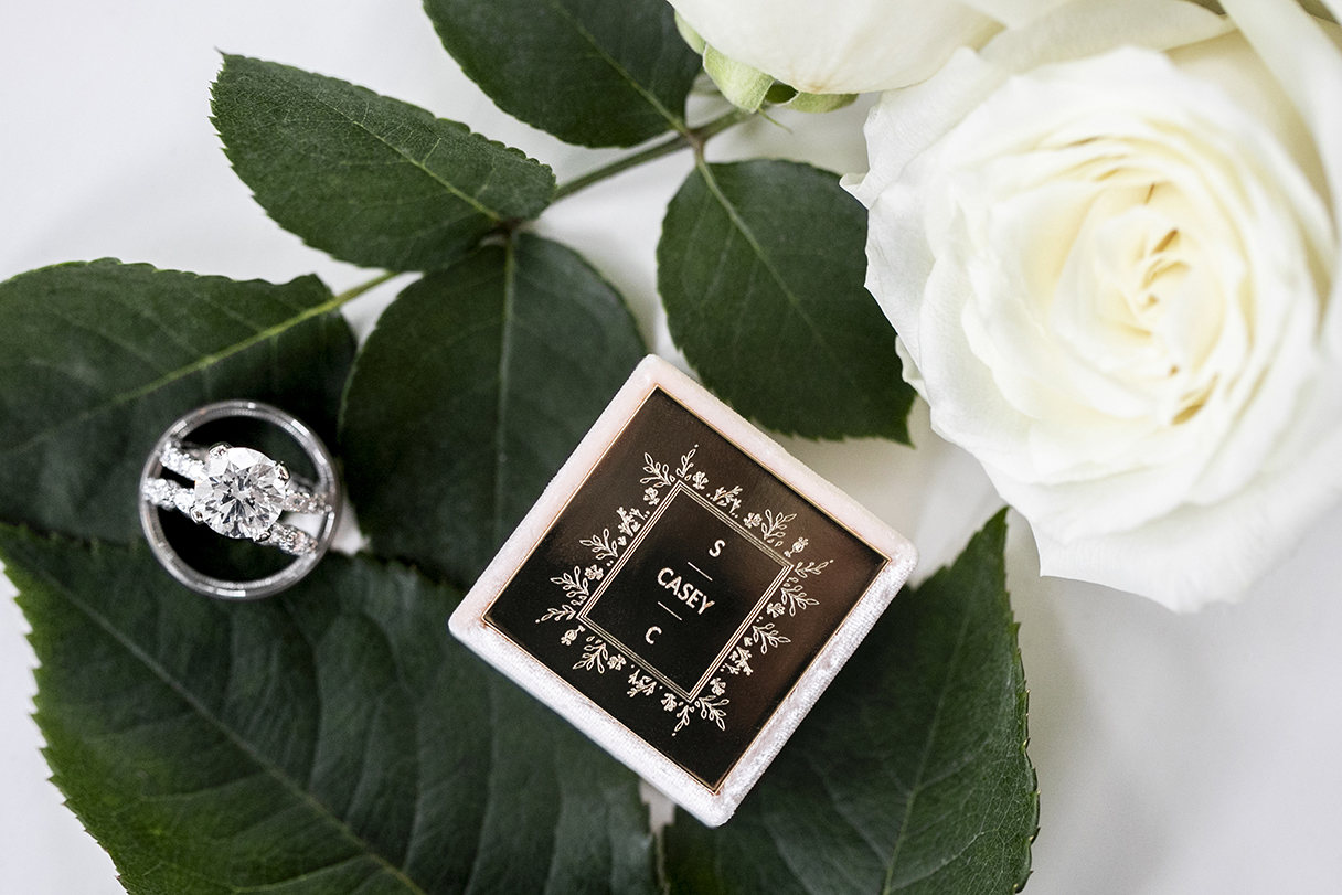 beautiful diamond ring shot on the stem of a white rose- photo by Anna Schmidt Photography
