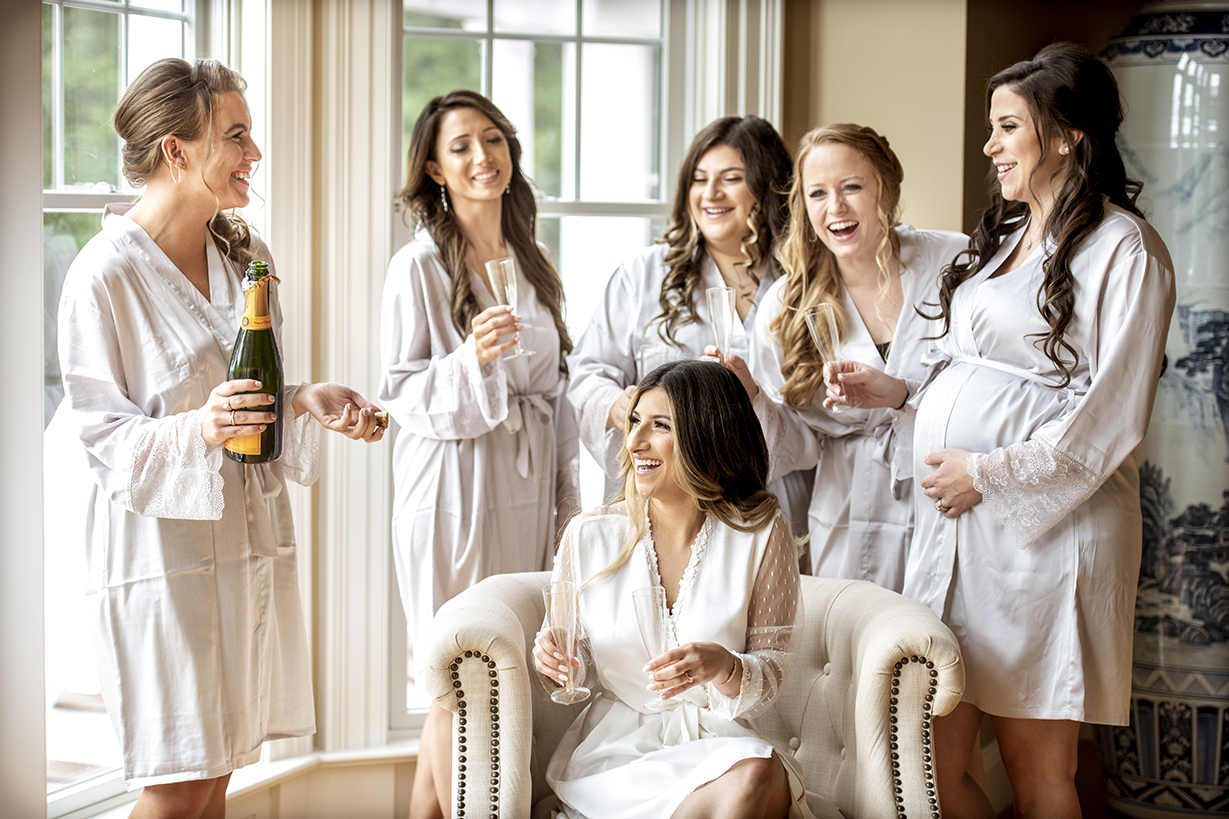 Bride and bridesmaids in robes sharing bubbly - photo by Anna Schmidt Photography