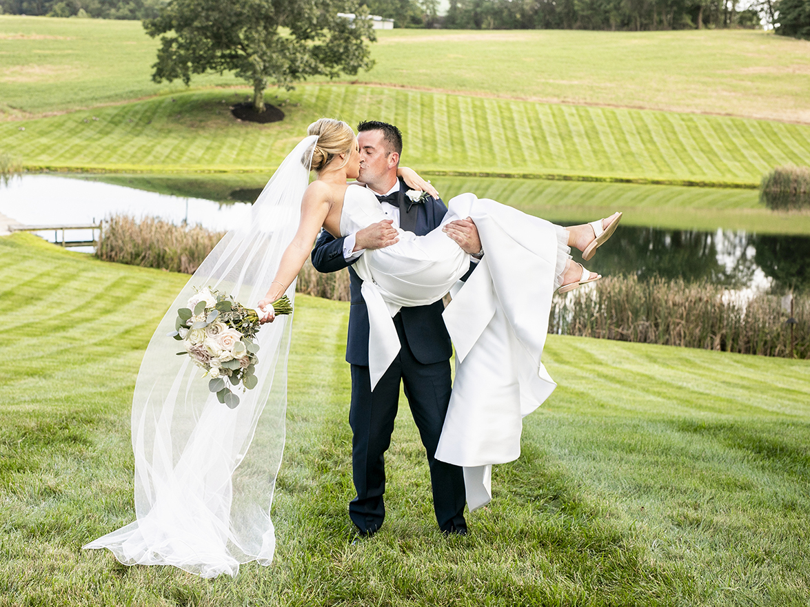 groom picking up his bride and giving her a big kiss- photo by Anna Schmidt Photography