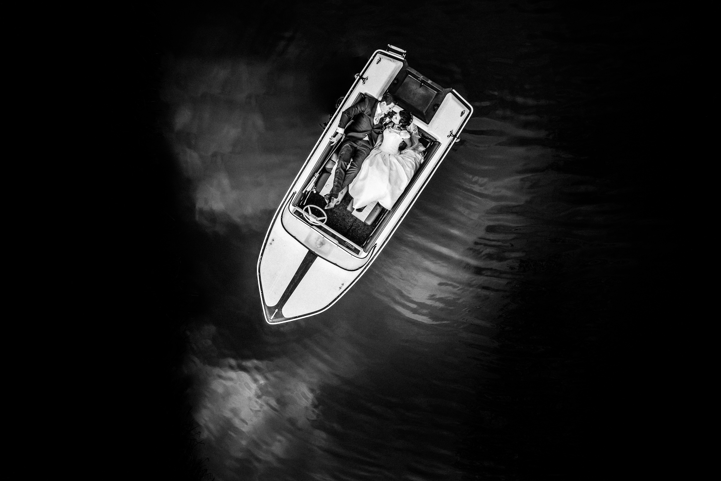 Aerial view of couple in small boat on water - photo by Peter van der Lingen Wedding Photography