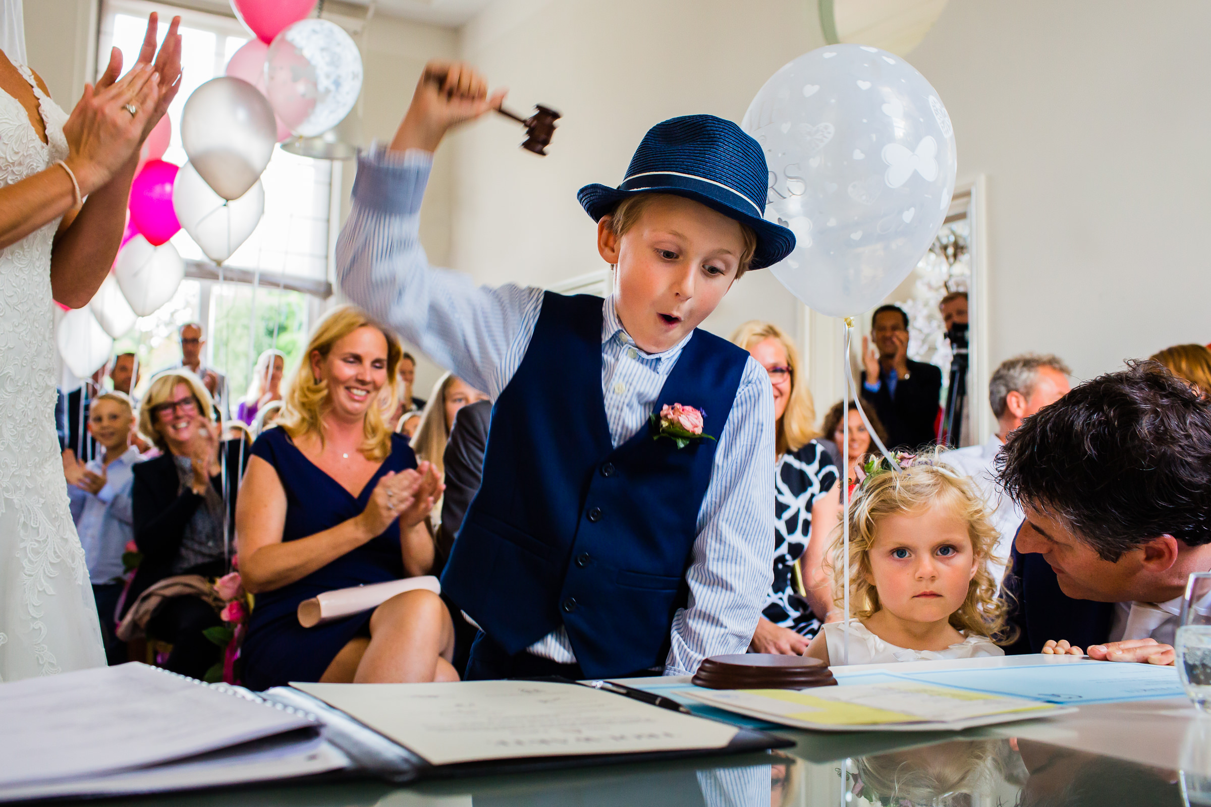 Boy using gavel at ceremony with little sister and father- photo by Peter van der Lingen Wedding Photography