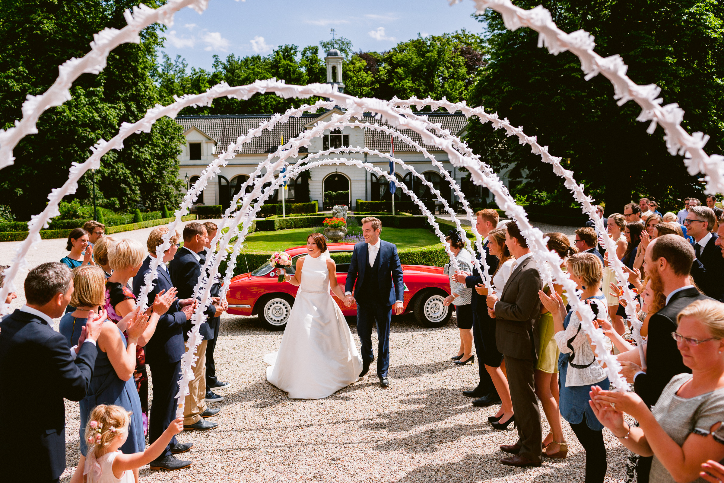 Bride and groom enter through decorative white hoops - photo by Peter van der Lingen Wedding Photography