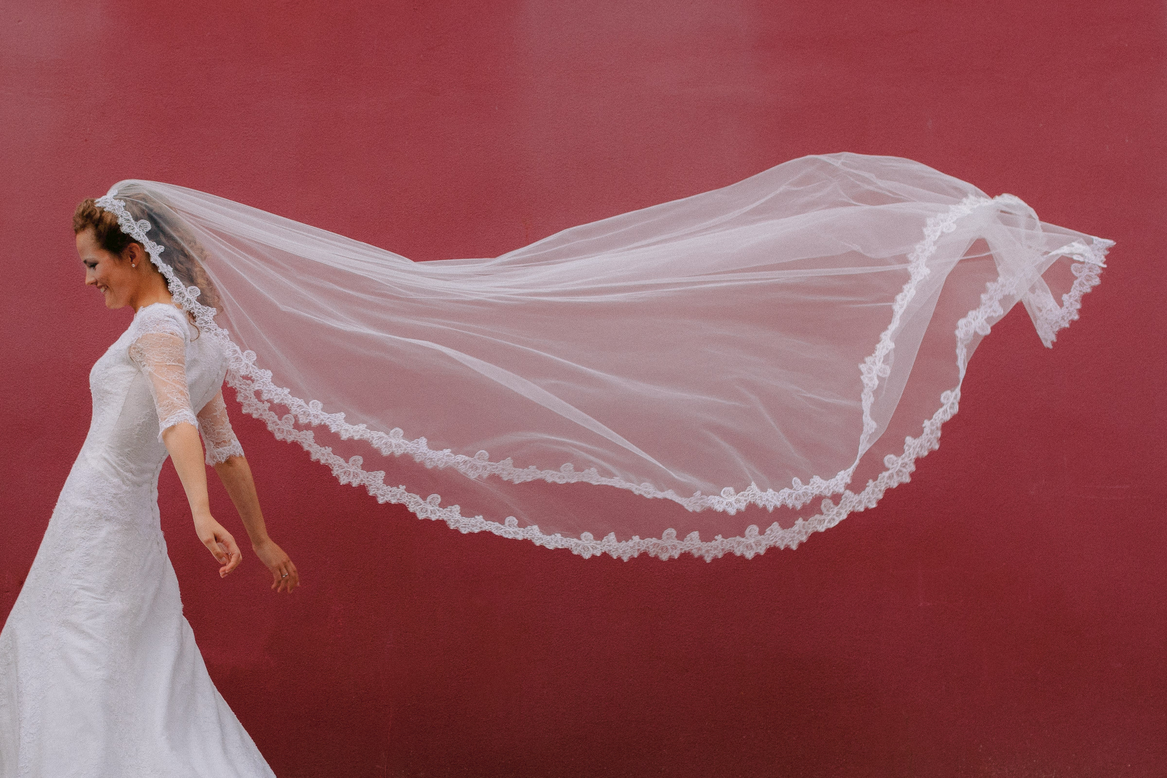 Bride in motion with long veil trailing behind - photo by Peter van der Lingen Wedding Photography