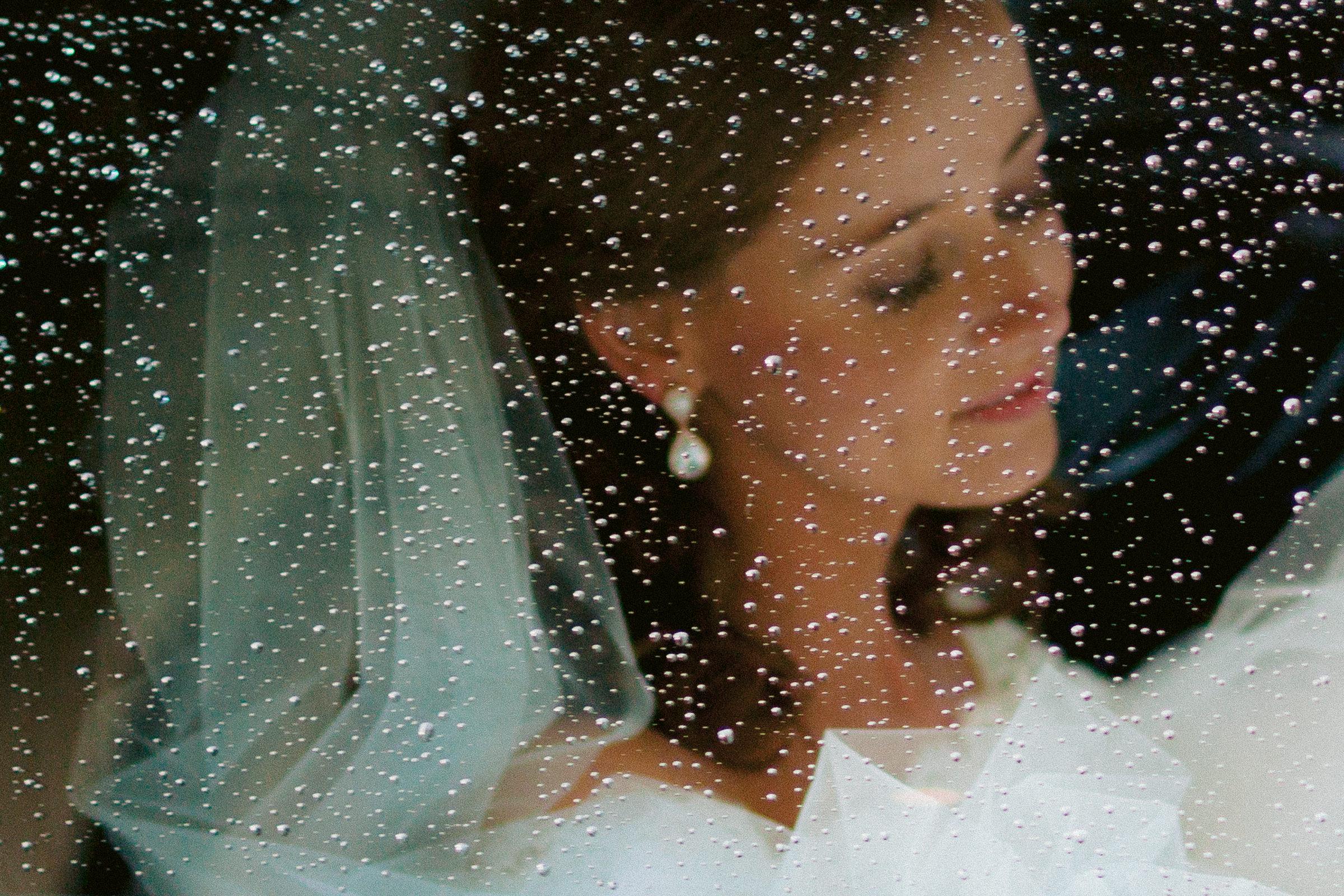 Bride through car window with raindrops - photo by Peter van der Lingen Wedding Photography