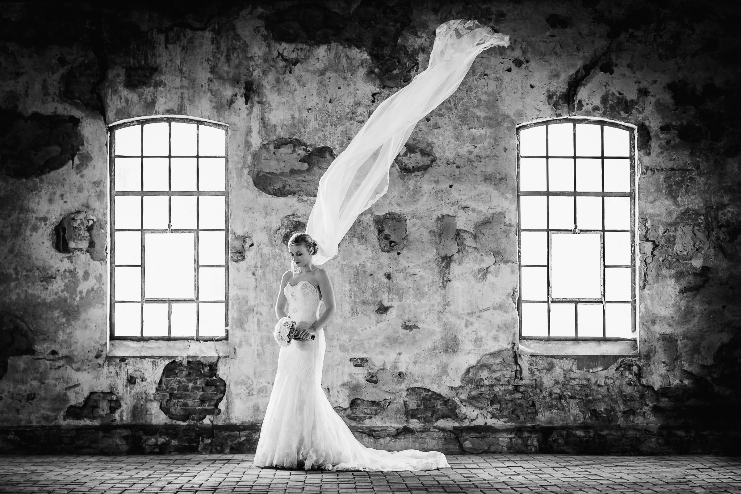 Bride with airborne veil against crumbling interior wall - photo by Peter van der Lingen Wedding Photography