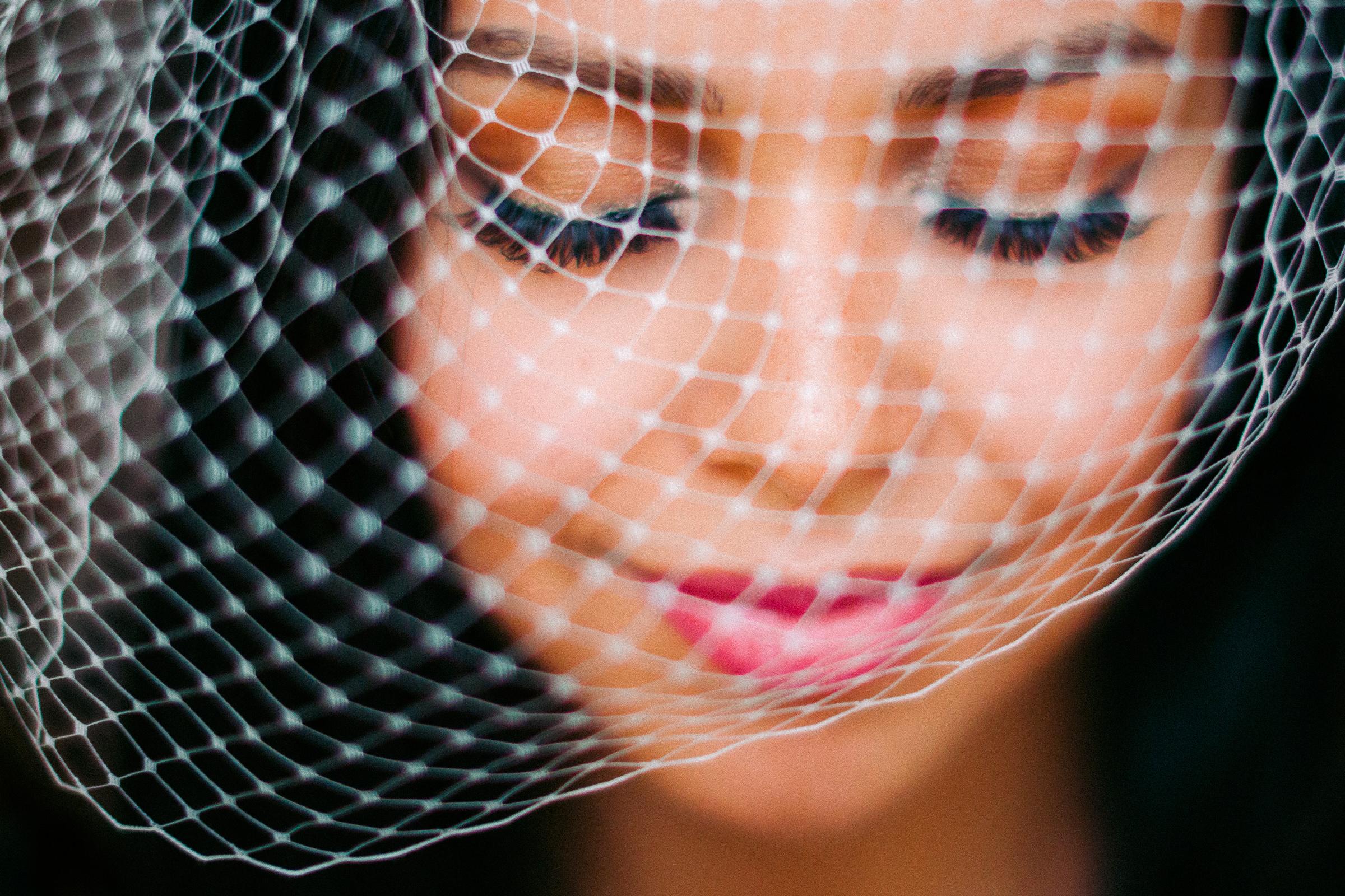 Closeup of smiling bride in birdcage veil - photo by Peter van der Lingen Wedding Photography