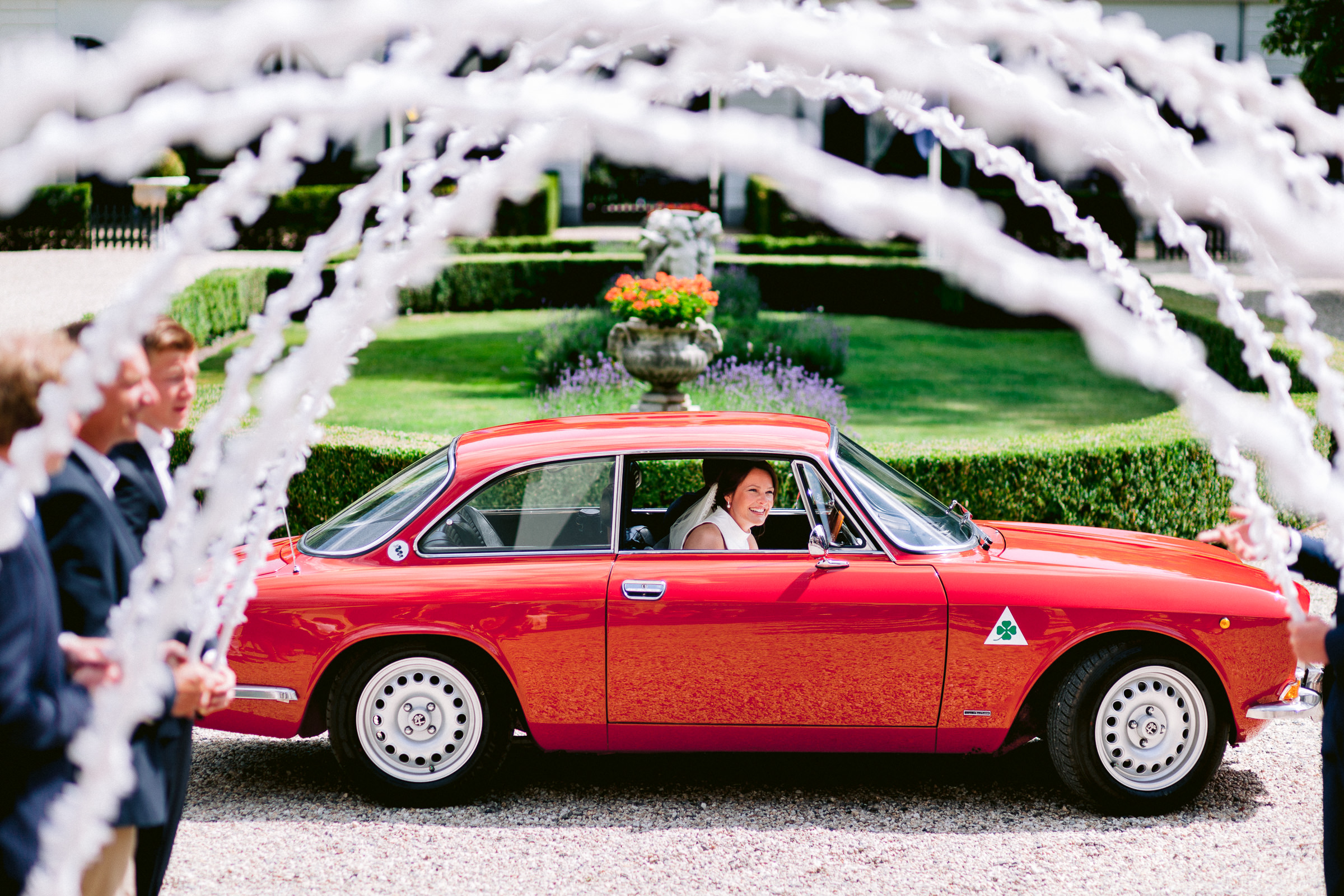 Couple arriving  in red car viewing white floral arches - photo by Peter van der Lingen Wedding Photography