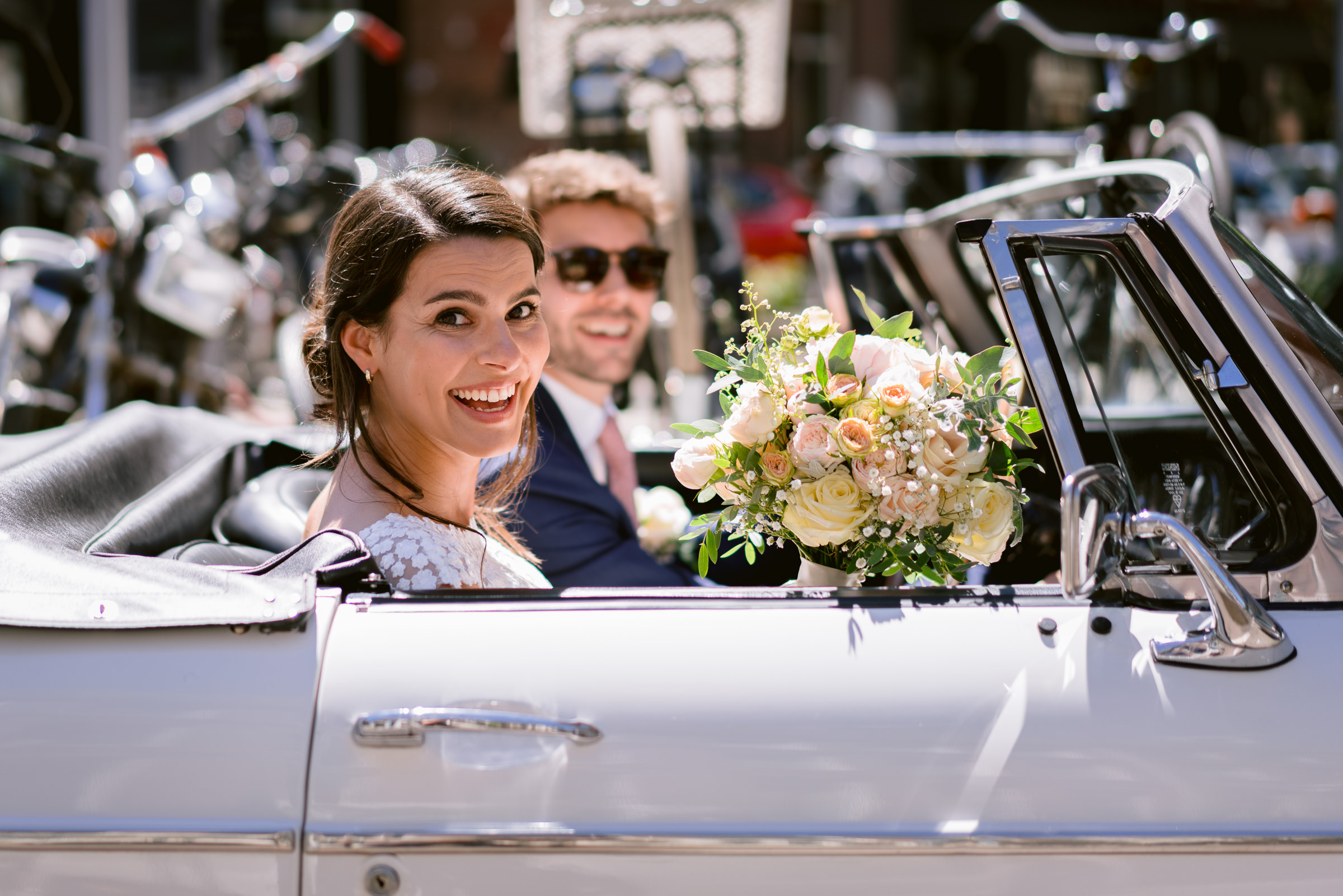 Couple exit in vintage car - photo by Peter van der Lingen Wedding Photography