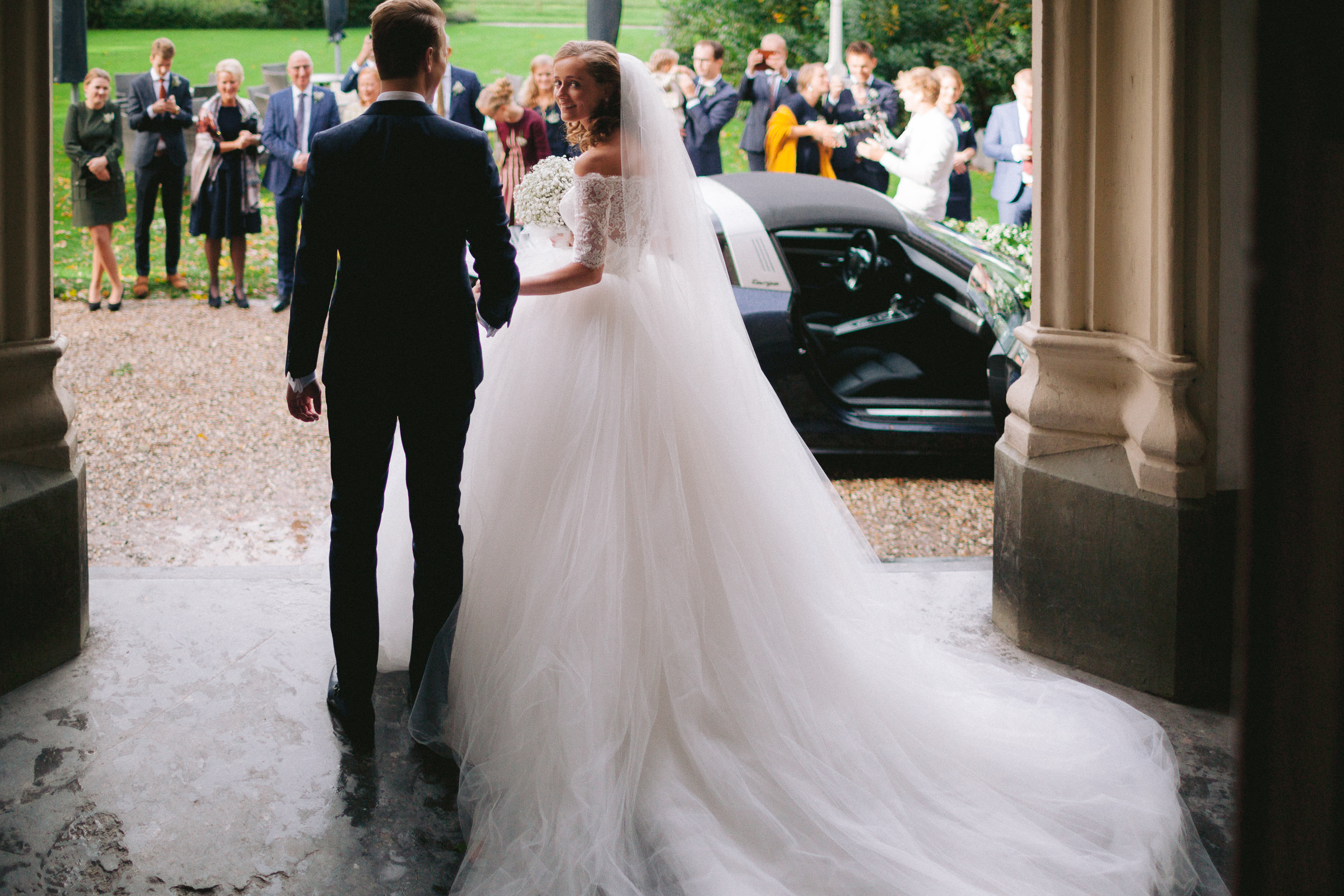 Groom exits to limo with bride in luxury gown - photo by Peter van der Lingen Wedding Photography