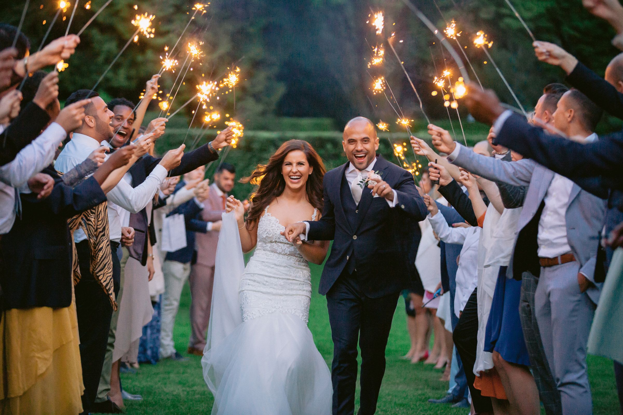Happy couple walking through tunnel of sparklers - photo by Peter van der Lingen Wedding Photography