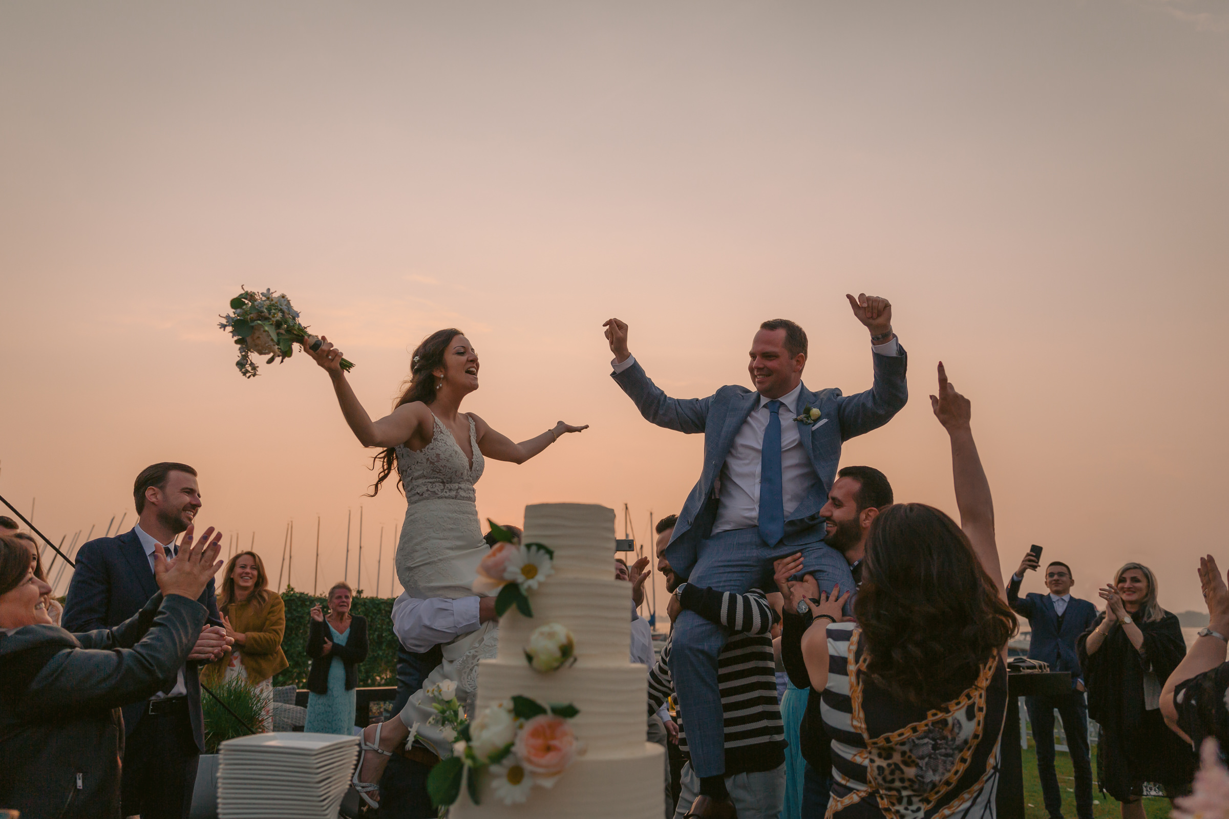 Outdoor bride and groom carried aloft by their cake - photo by Peter van der Lingen Wedding Photography