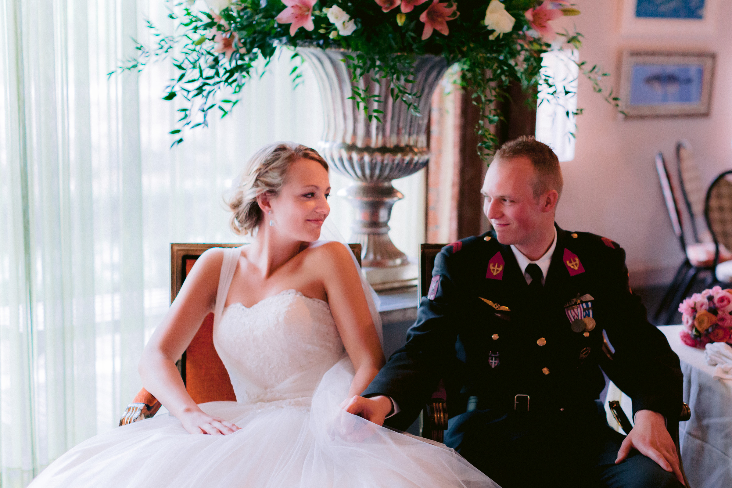 Sassy seated bride with military groom - photo by Peter van der Lingen Wedding Photography