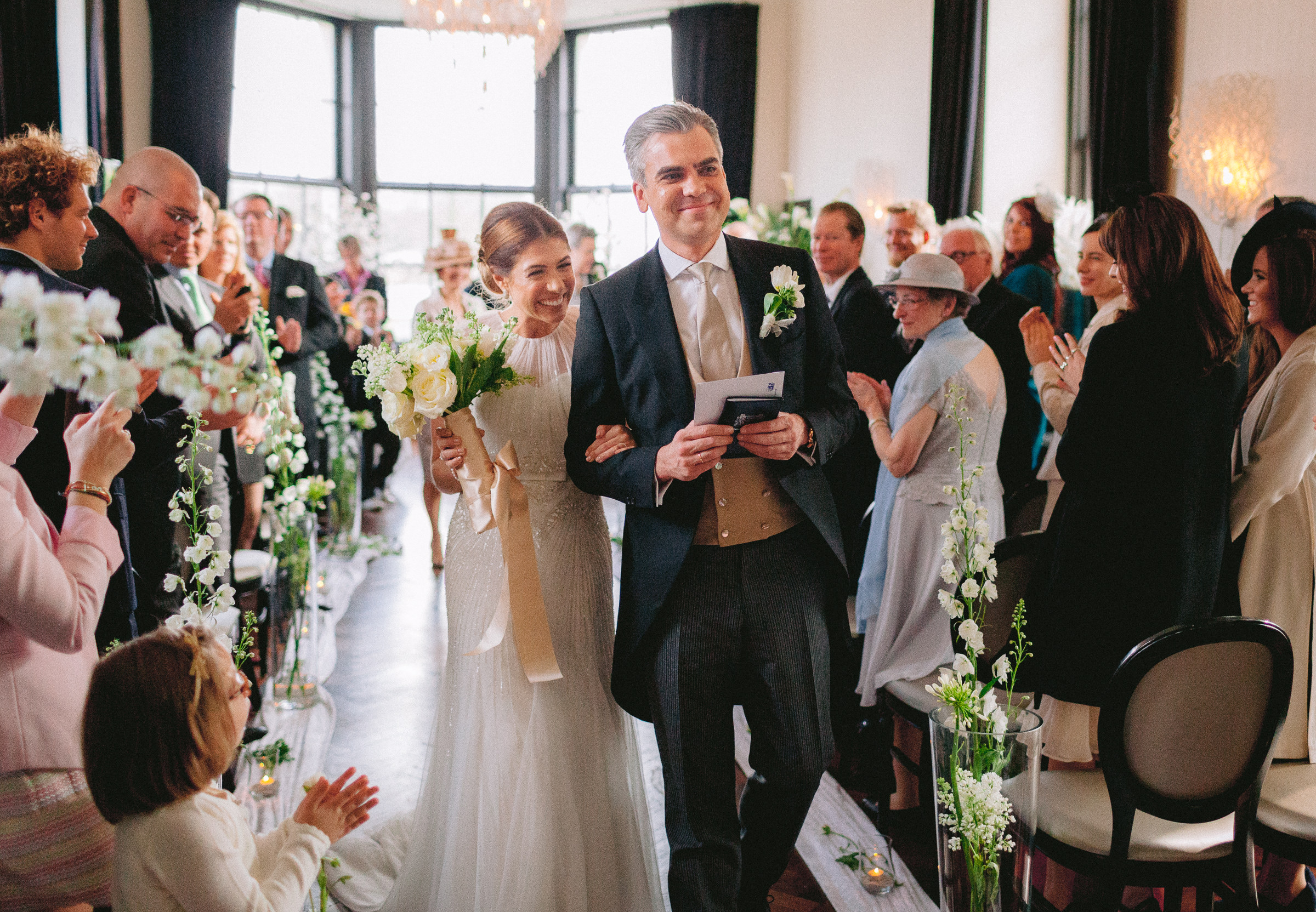 Smiling bride and groom recessional - photo by Peter van der Lingen Wedding Photography