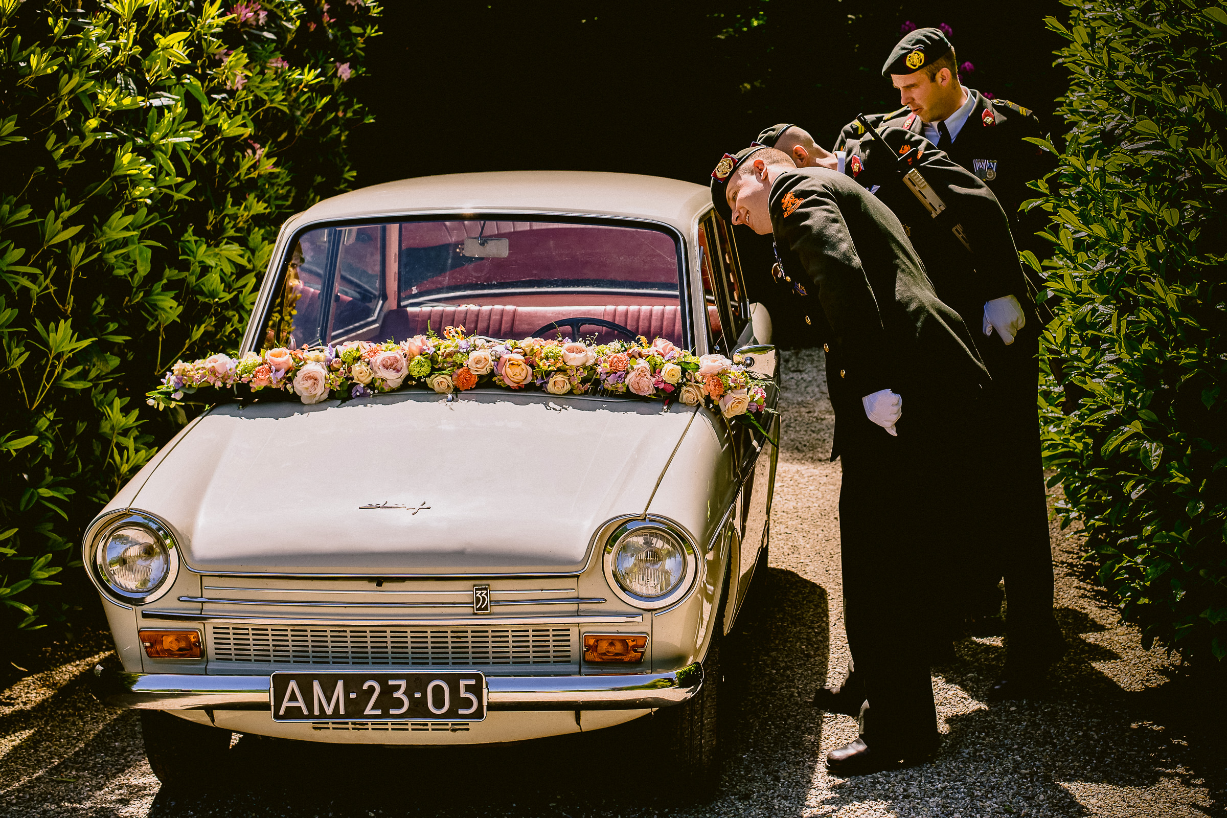 Uniformed men looking into vintage wedding car decorated with flowers - photo by Peter van der Lingen Wedding Photography