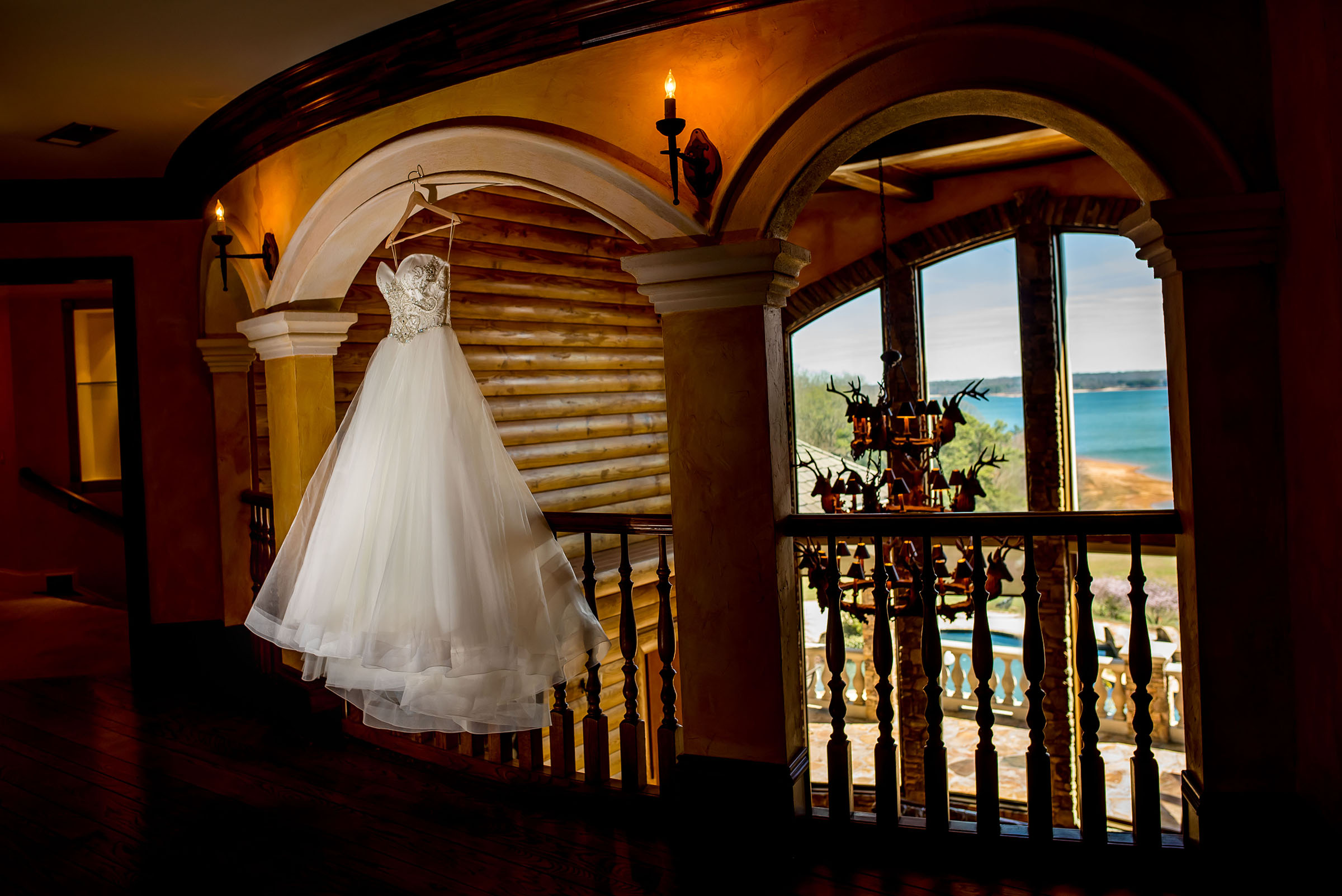 Bridal gown hanging by window with tropical view - photo by Gloria Ruth Photography