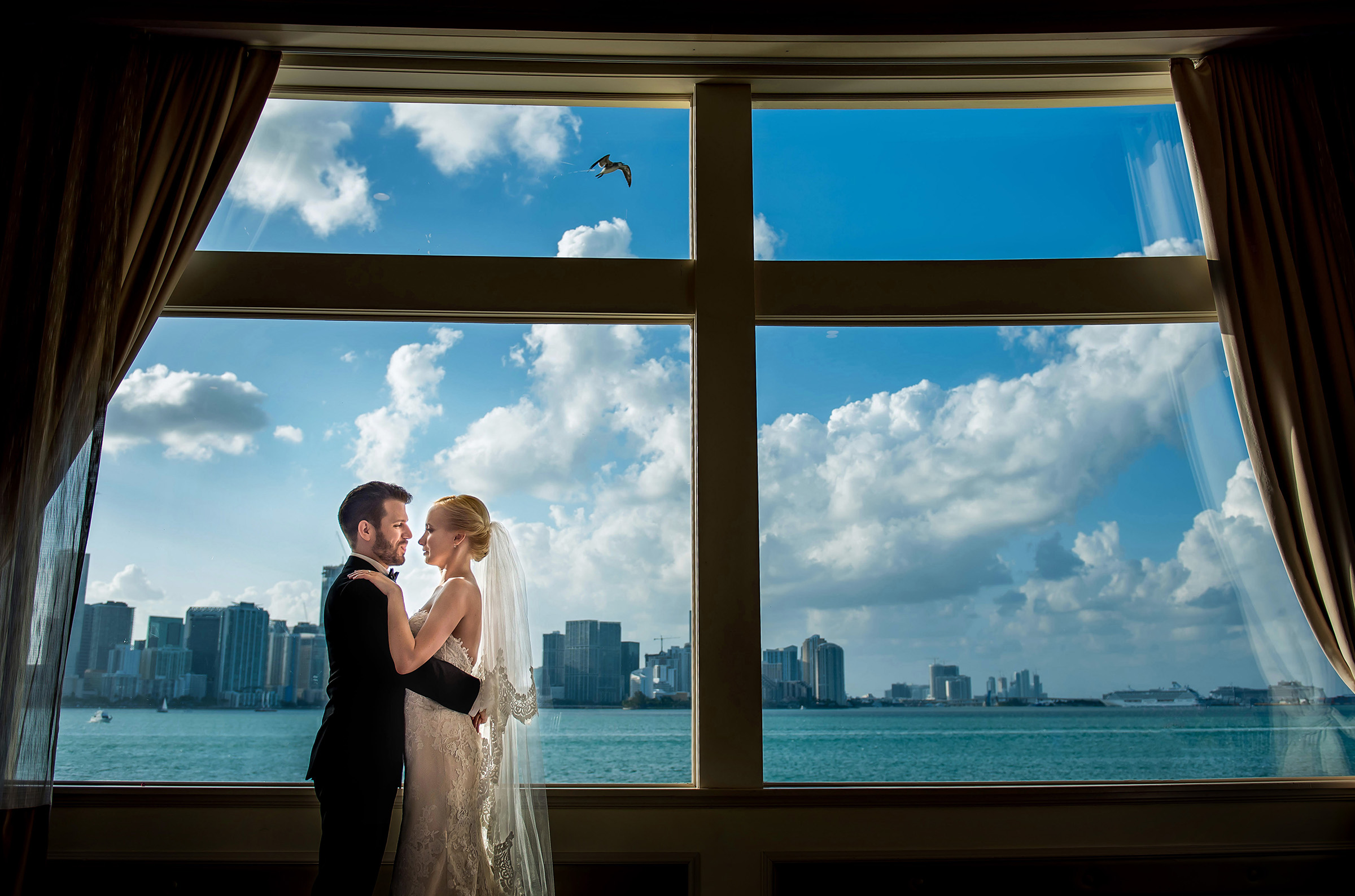 Couple portrait against water and skyline - photo by Gloria Ruth Photography