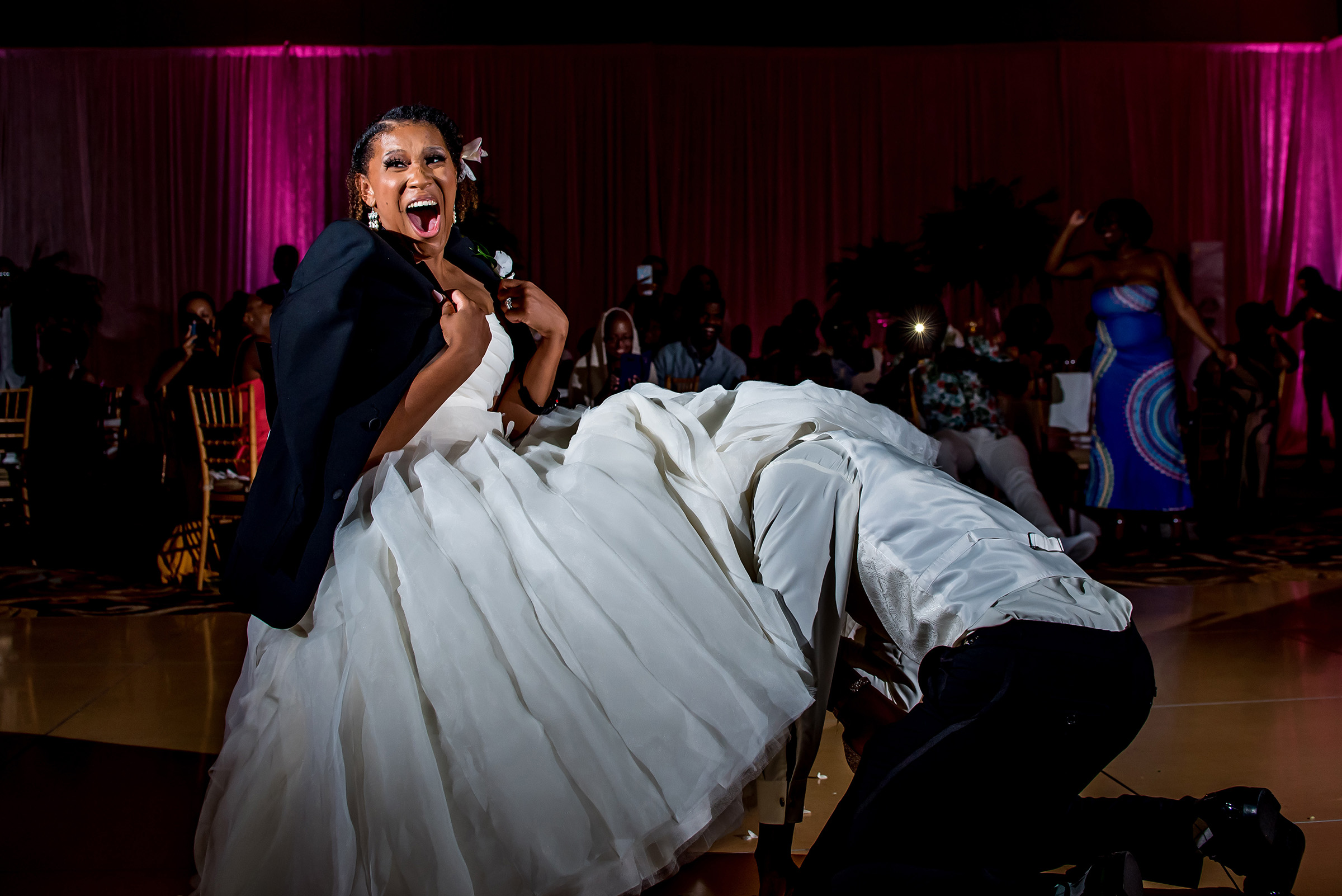 Hilarious shot of man under brides gown - photo by Gloria Ruth Photography