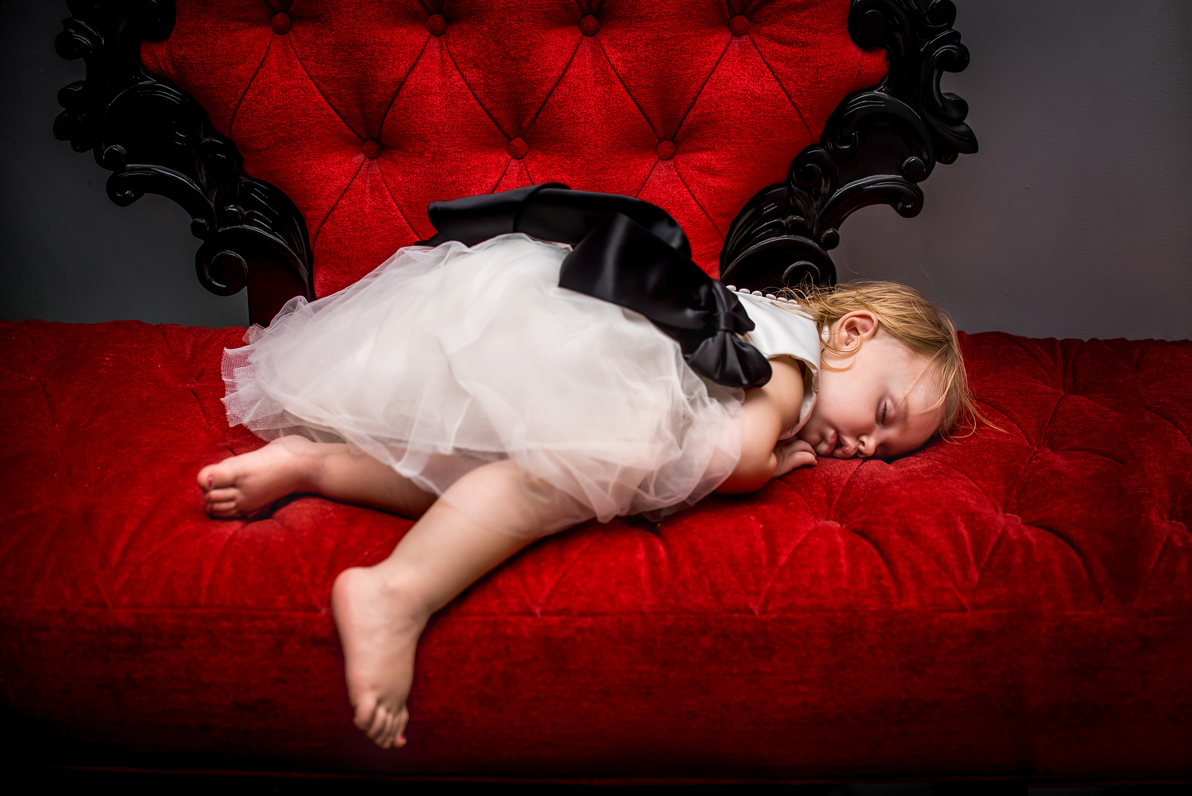 Little flower girl napping on velvet couch - photo by Gloria Ruth Photography