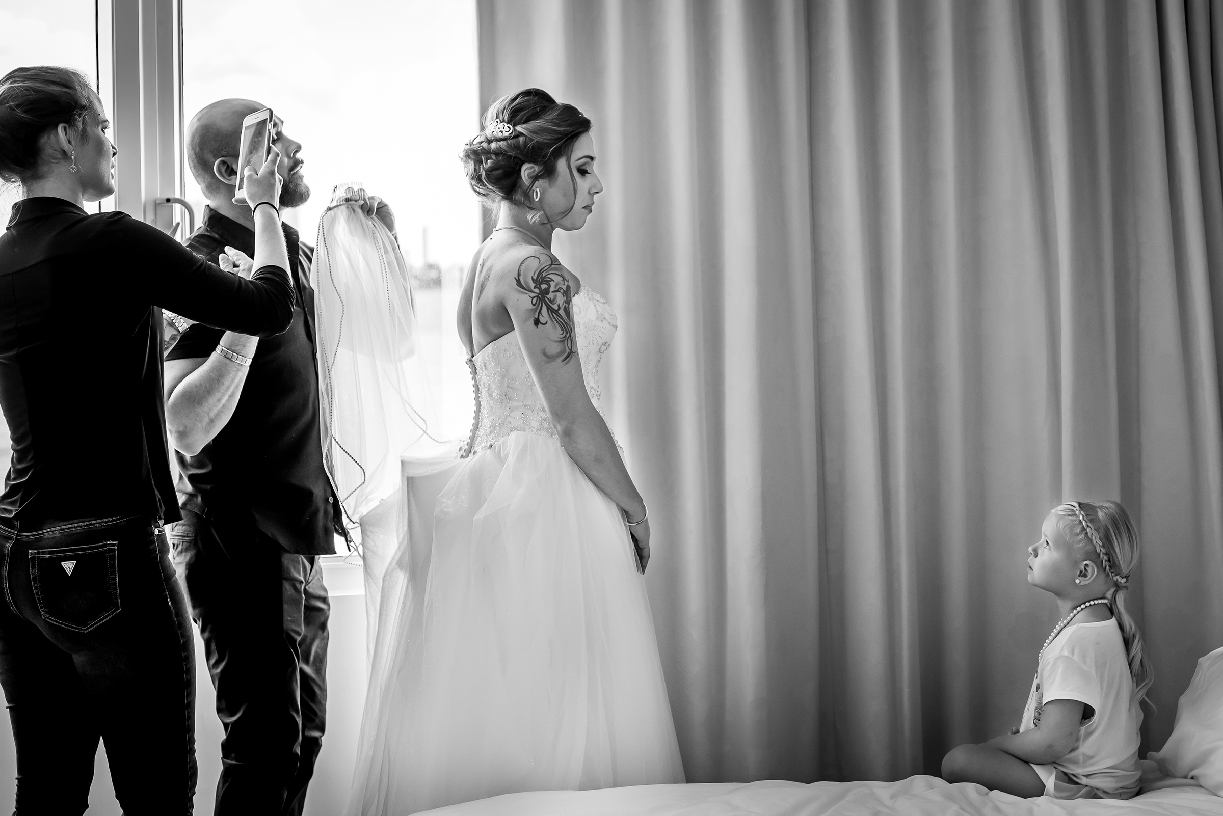 Little girl looking at bride getting dressed - photo by Gloria Ruth Photography
