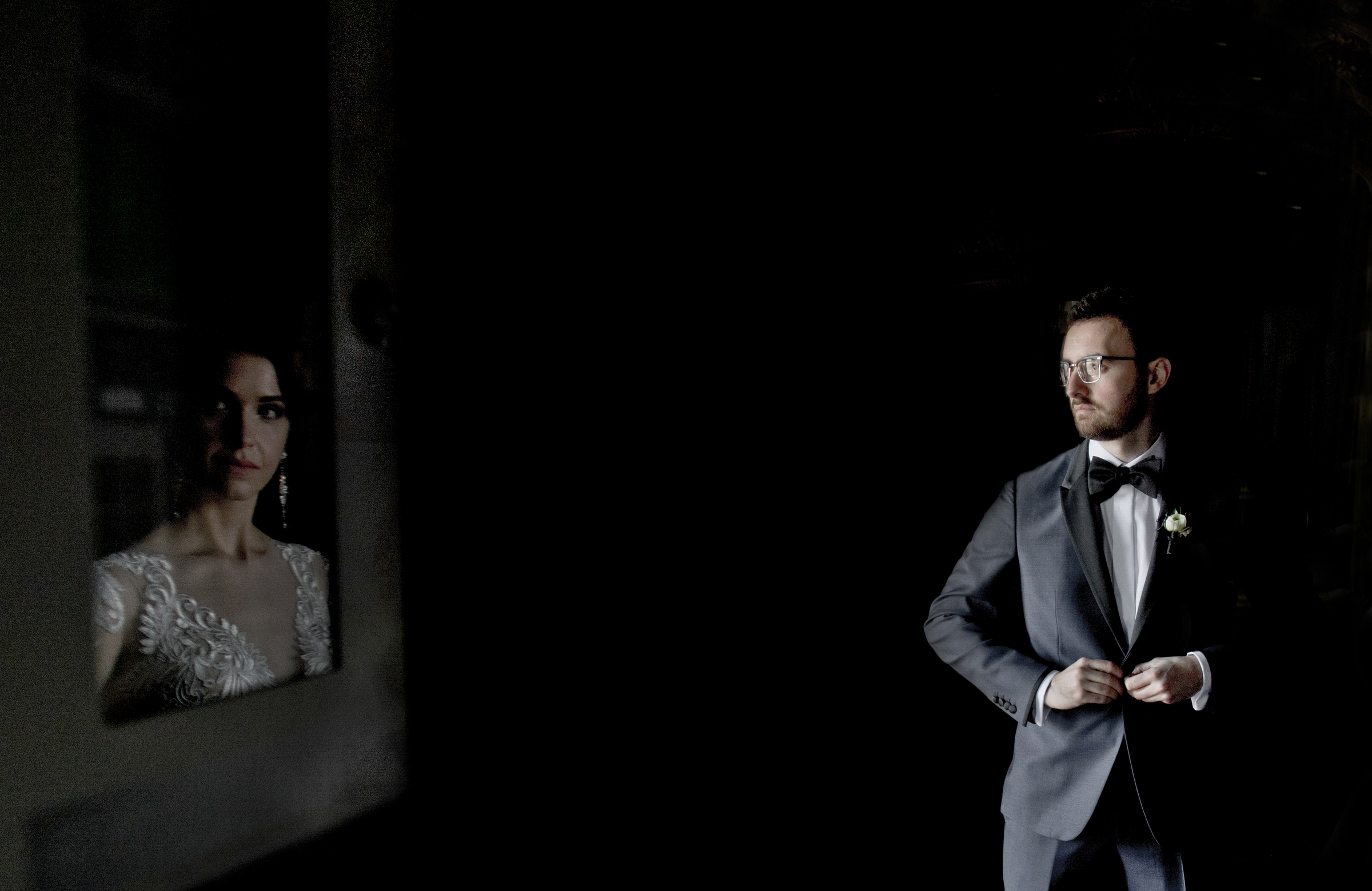 Bride reflected in mirror as groom buttons up jacket - photo by Matthew Sowa Photography