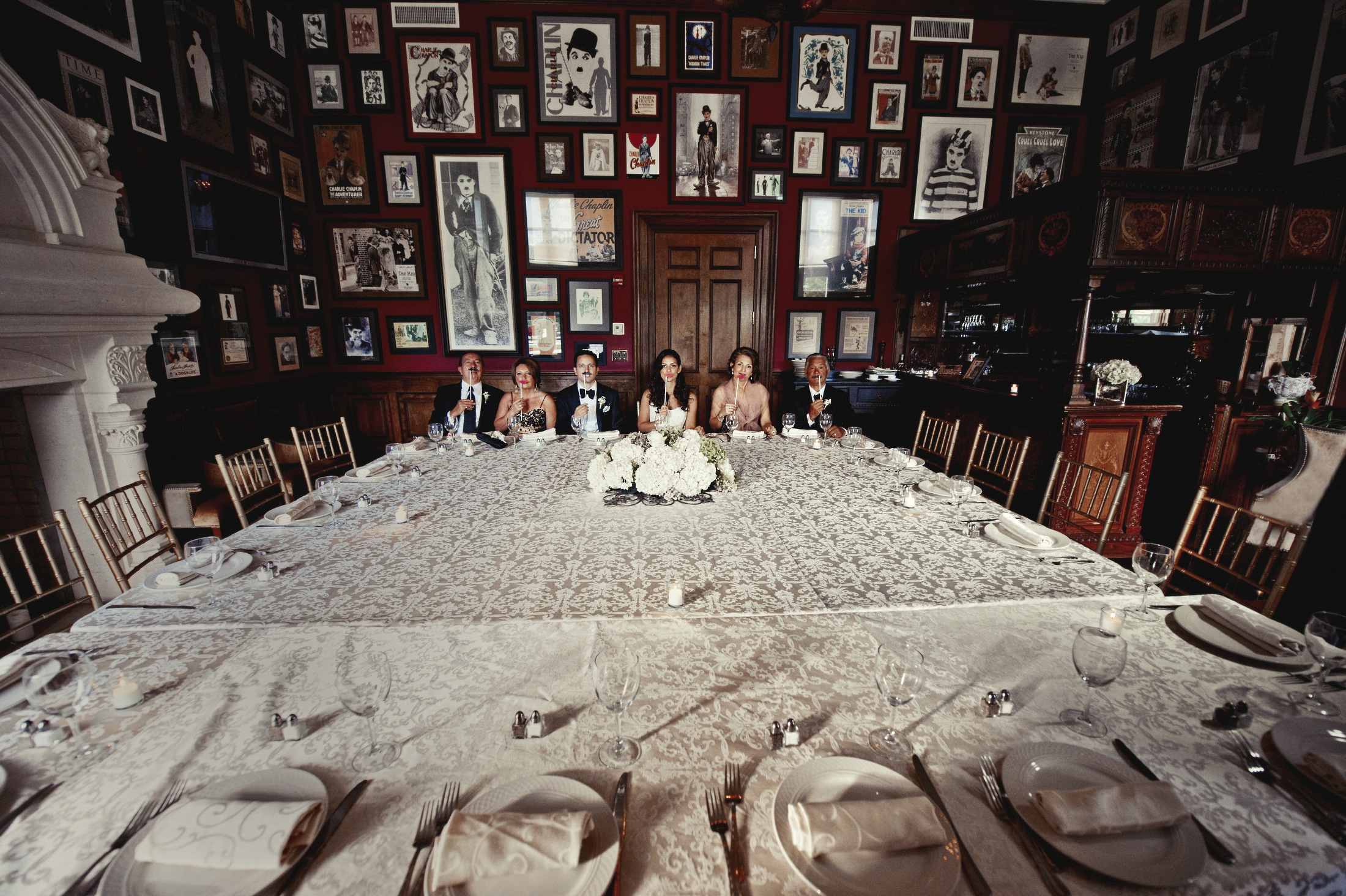 Couple and family at large set table surrounded by empty chairs - photo by Matthew Sowa Photography