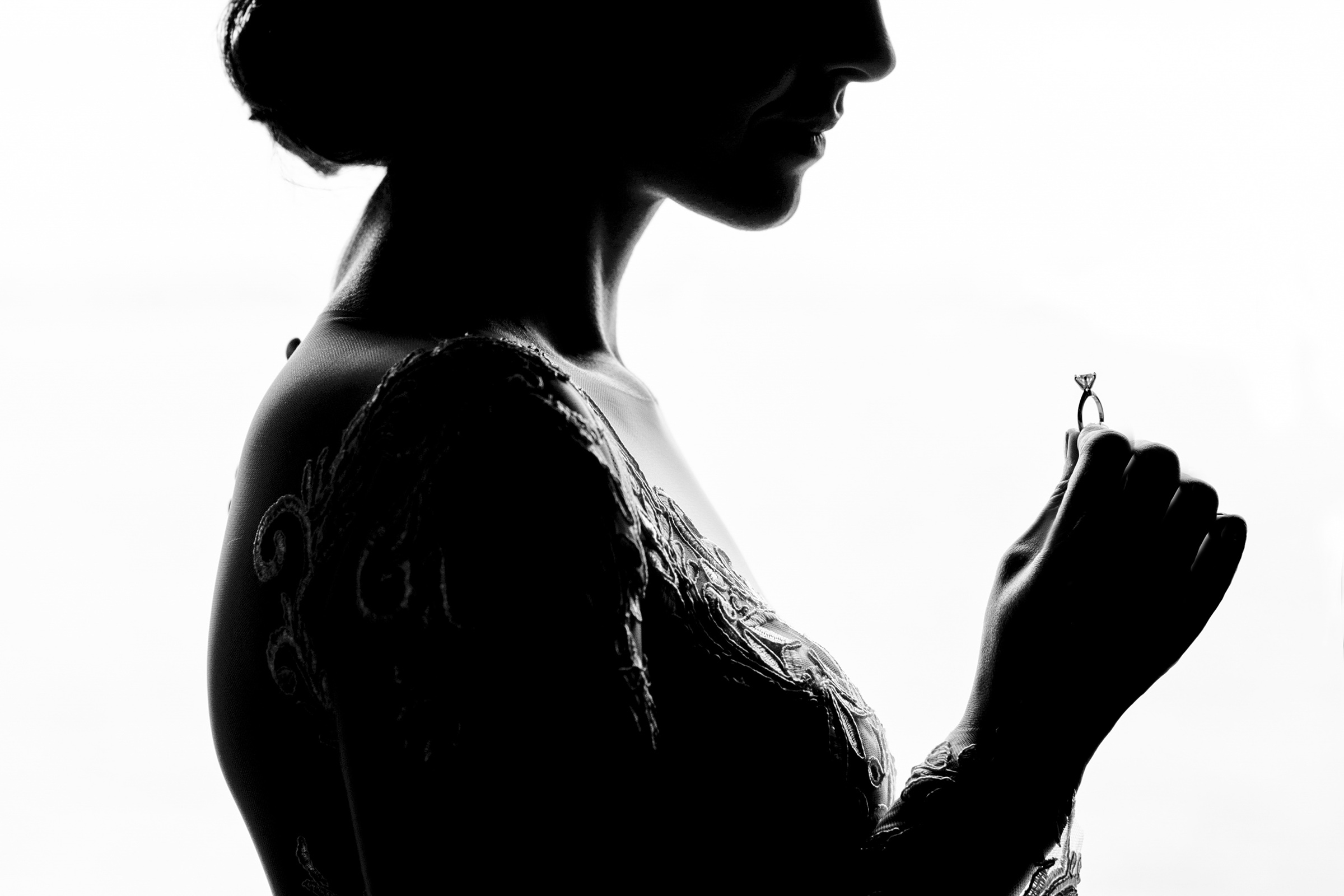 Partial silhouette bride holding diamond solitaire ring - photo by Matthew Sowa Photography