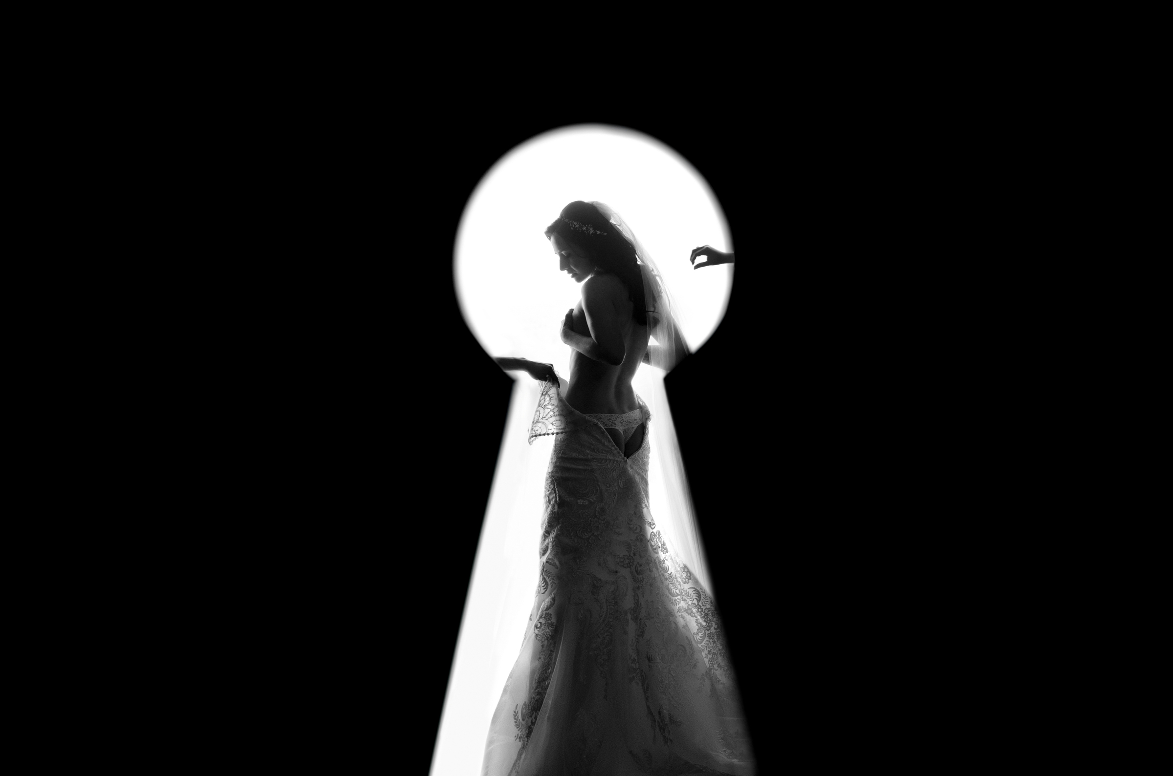 Seen through keyhole bride getting into her gown - photo by Matthew Sowa Photography