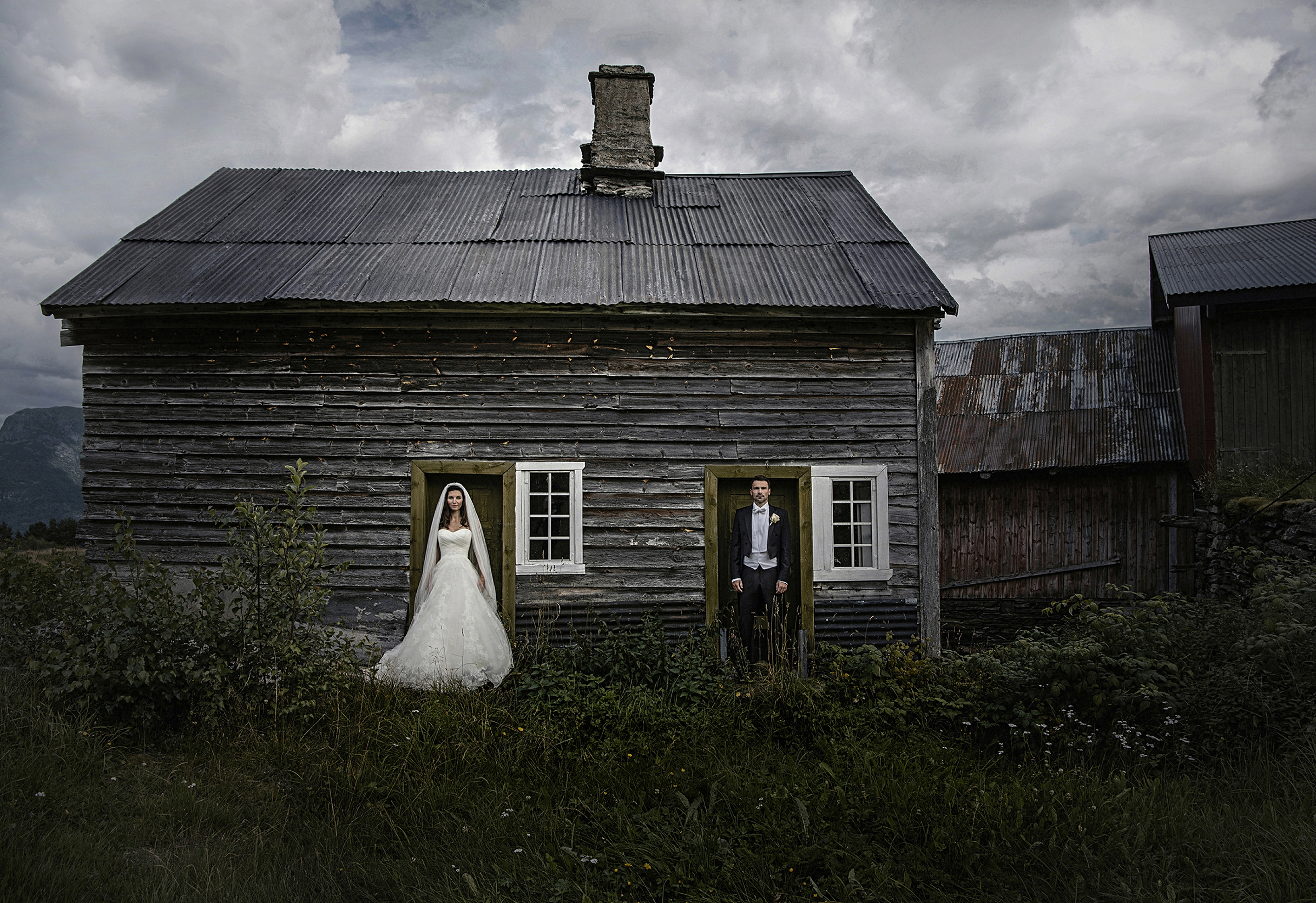 Couple pose against rustic cabin - photo by Frøydis