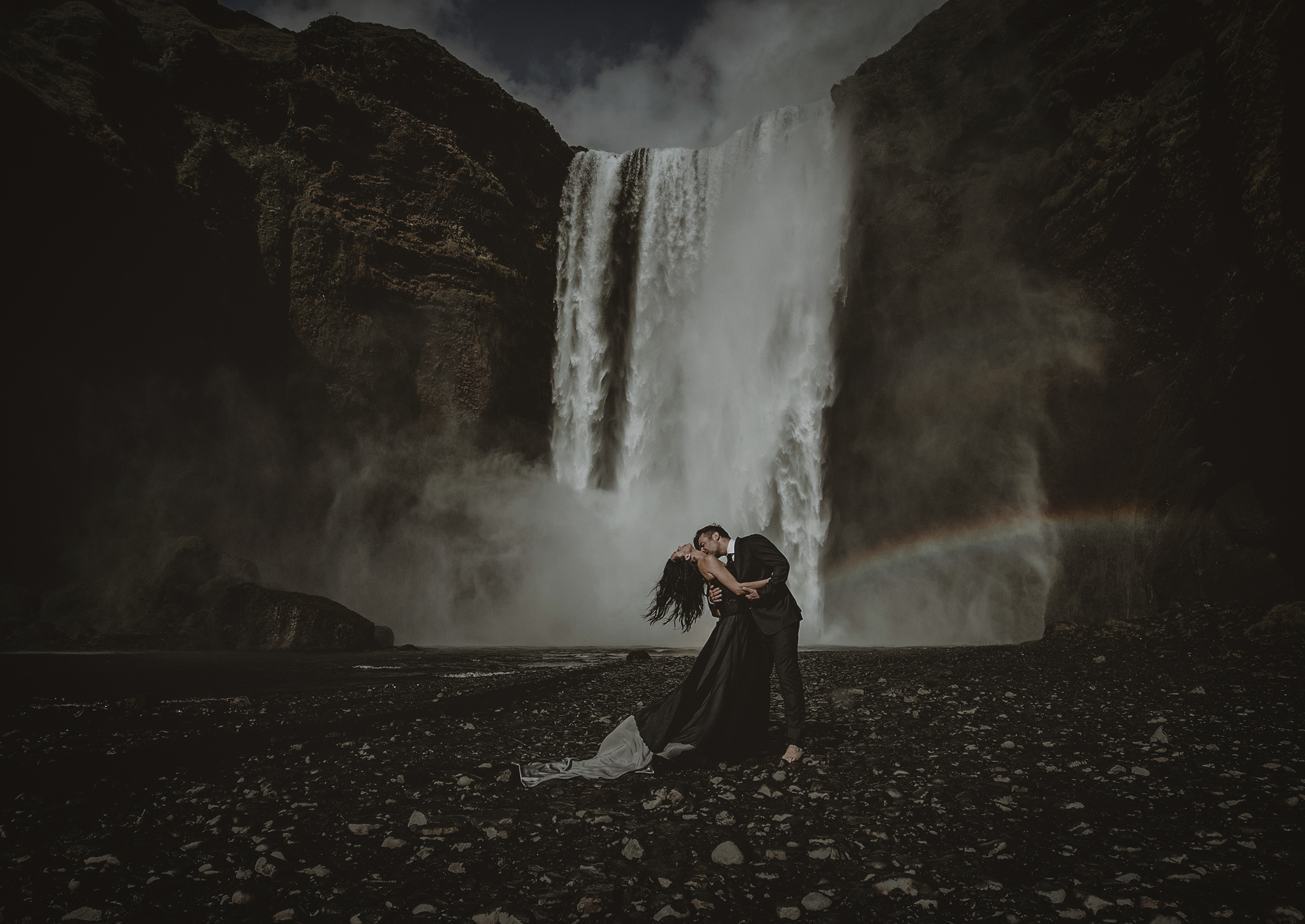 Dramatic kiss at waterfall with rainbow - photo by Frøydis