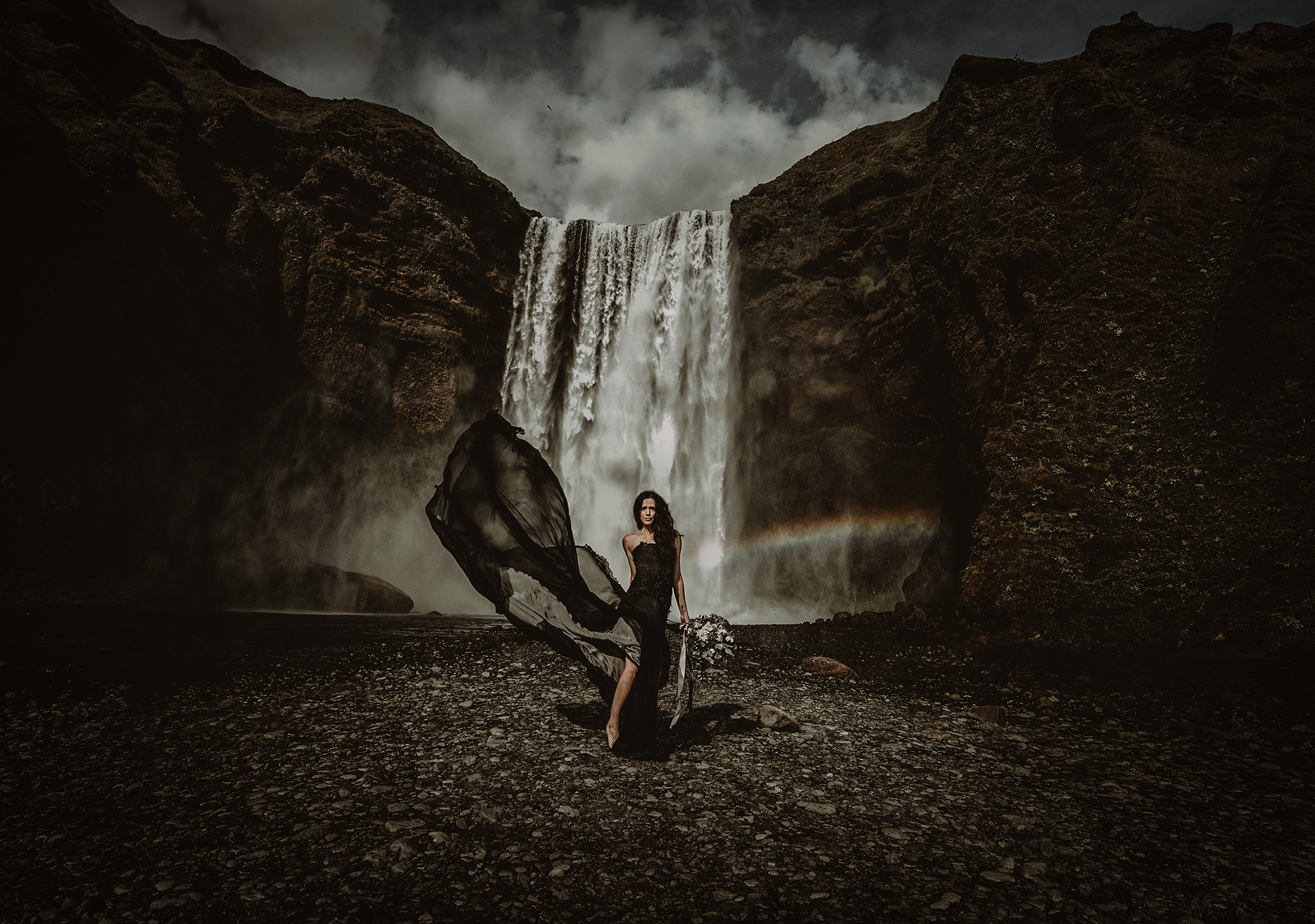 Elegant pose against waterfall with rainbow - photo by Frøydis