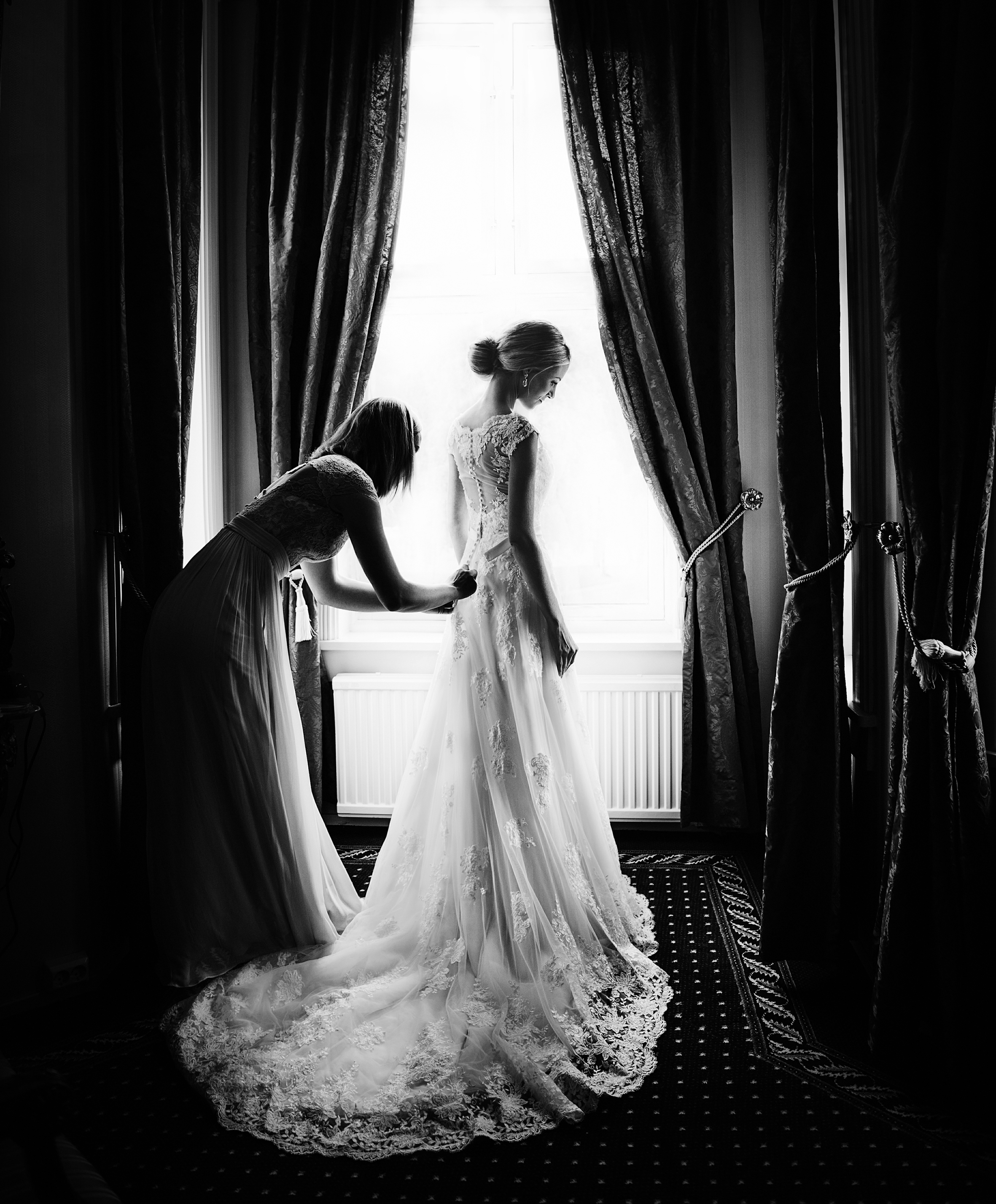 Finishing touches for bride in window light with drapes - photo by Frøydis