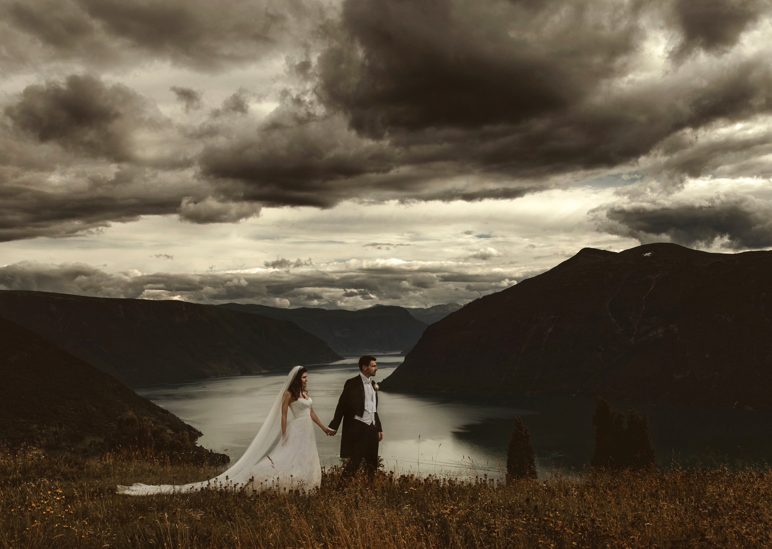 Hand in hand couple against stormy mountain skies - photo by Frøydis