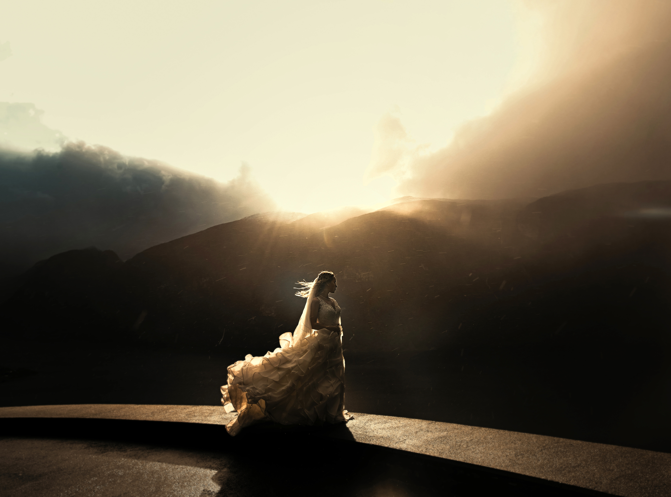 Painterly bride portrait against dramatic mountain lighting  - photo by Frøydis
