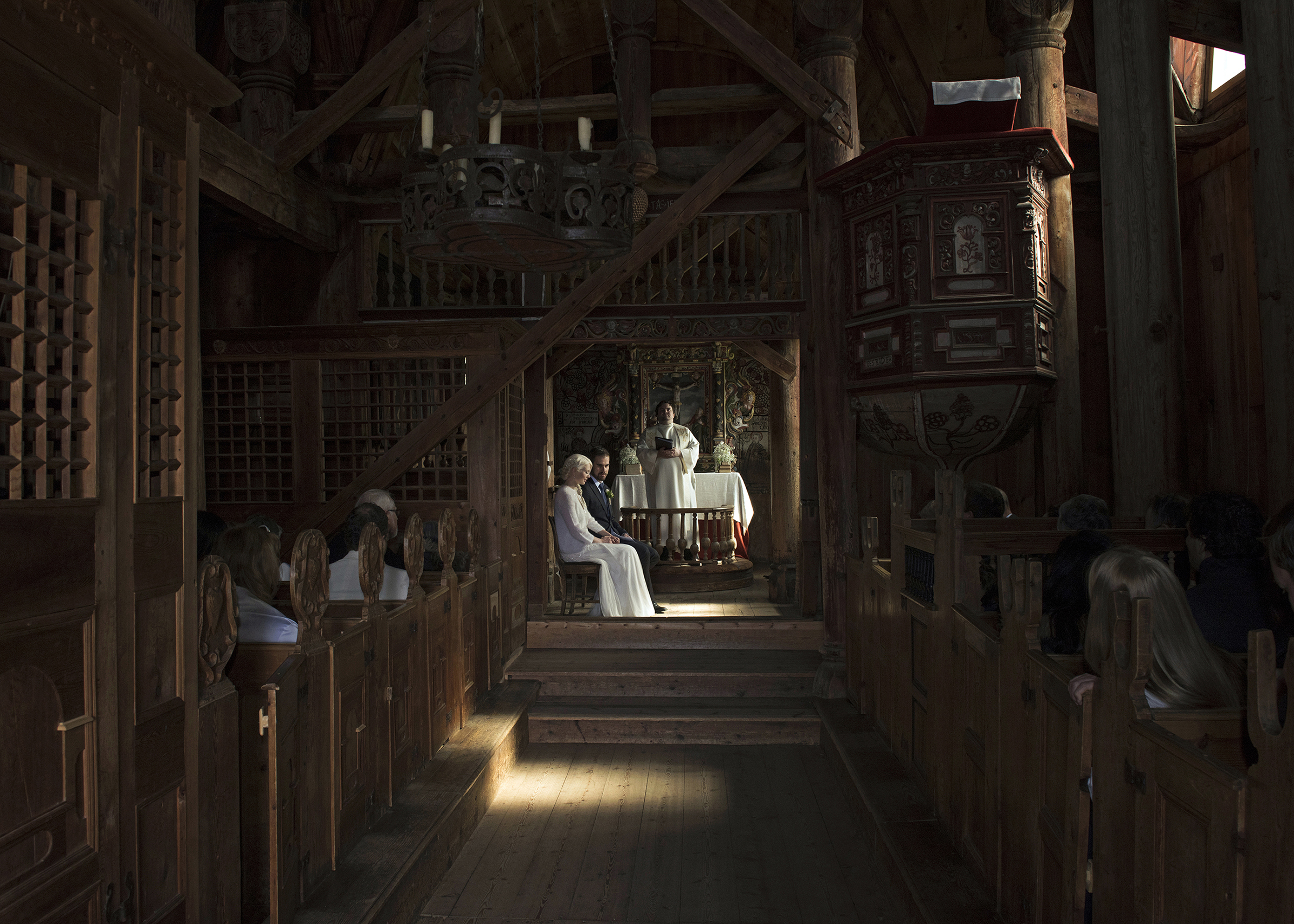 Painterly portrait of ceremony couple and officiant in rustic wooden church - photo by Frøydis