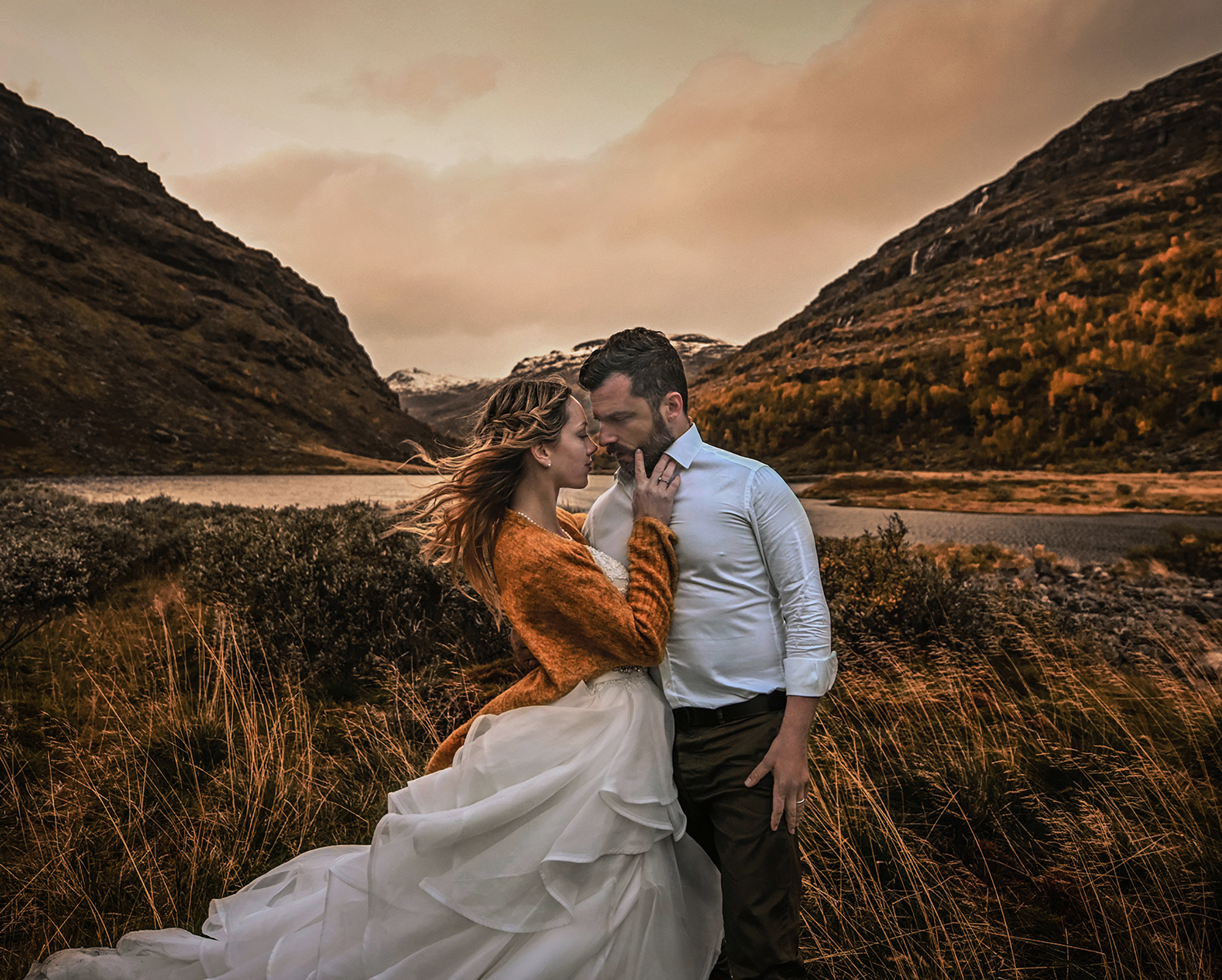 Windswept outdoor kiss against mountain scenery - photo by Frøydis