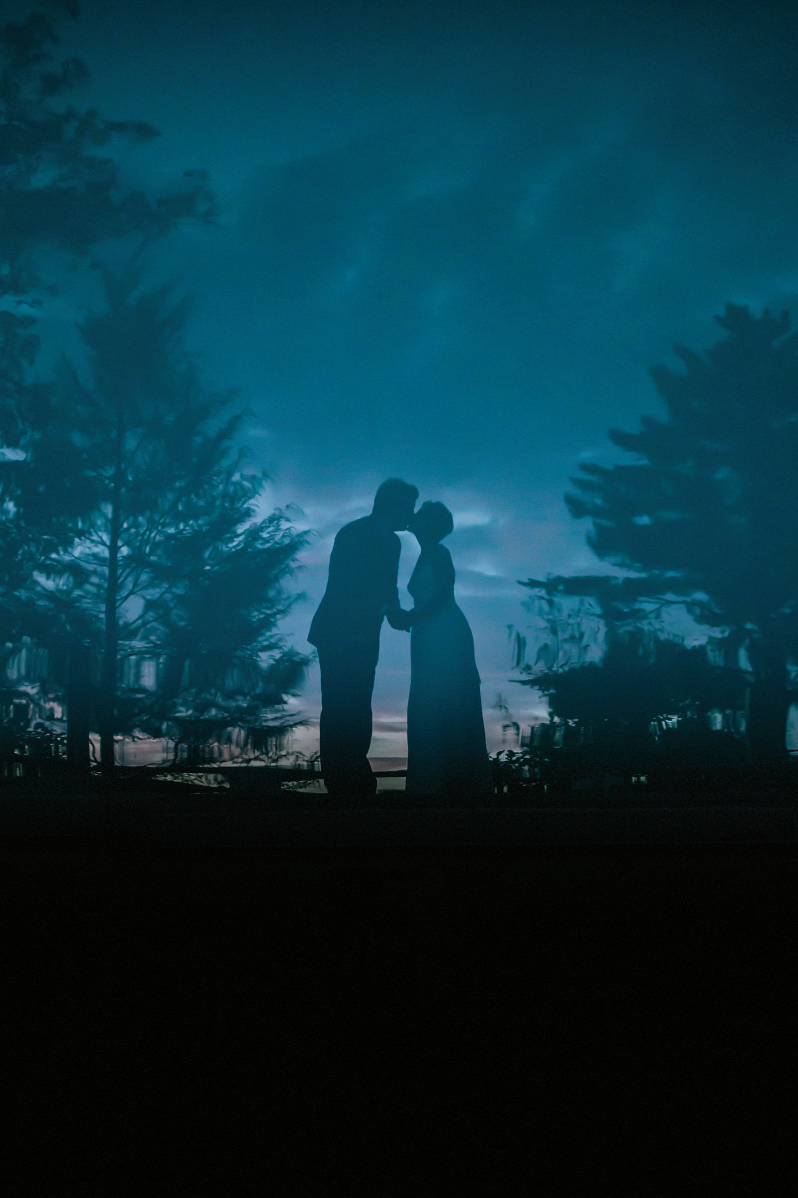 Blue light silhouette of couple kissing - photo by Jonas Seaman Photography